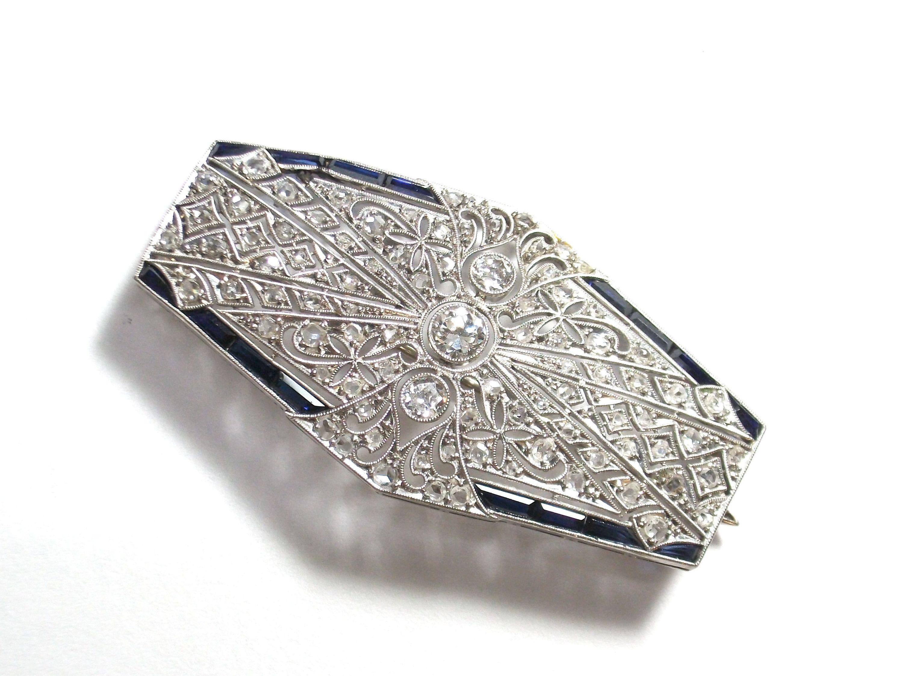 Broche Art Decó realizado en platino con tres brillantes, diamantes talla rosa y zafiros calibrados. Circa 1920-1930. VENDIDO