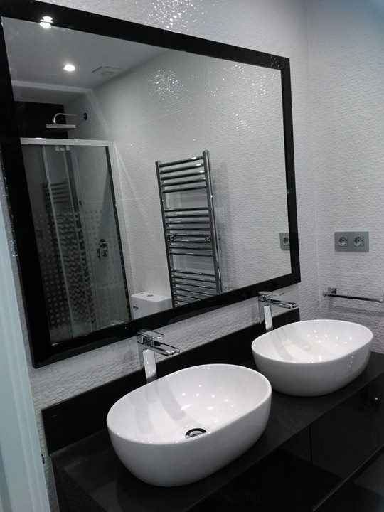 Baño. Detalle de espejo y lavabos