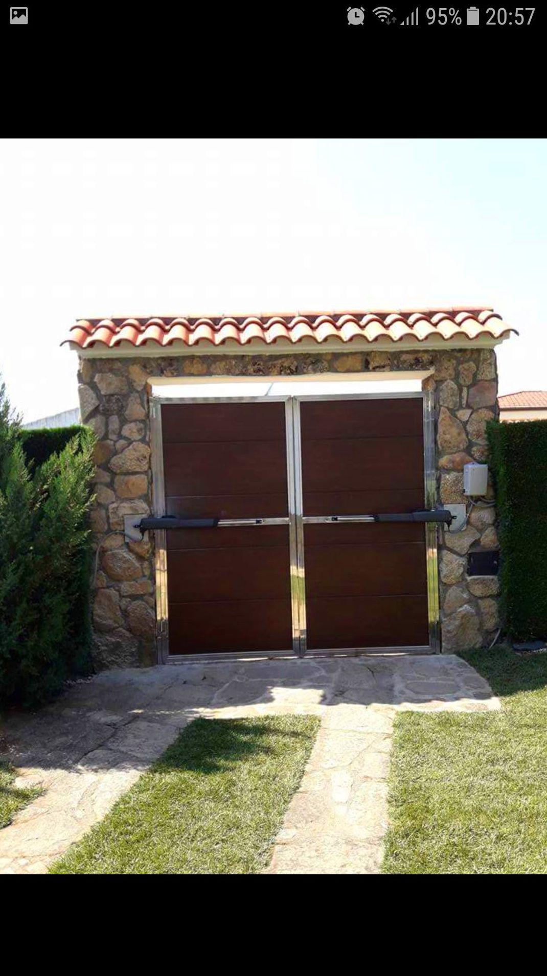 Puerta de acero inoxidable, panel abatible con motores hidráulicos.