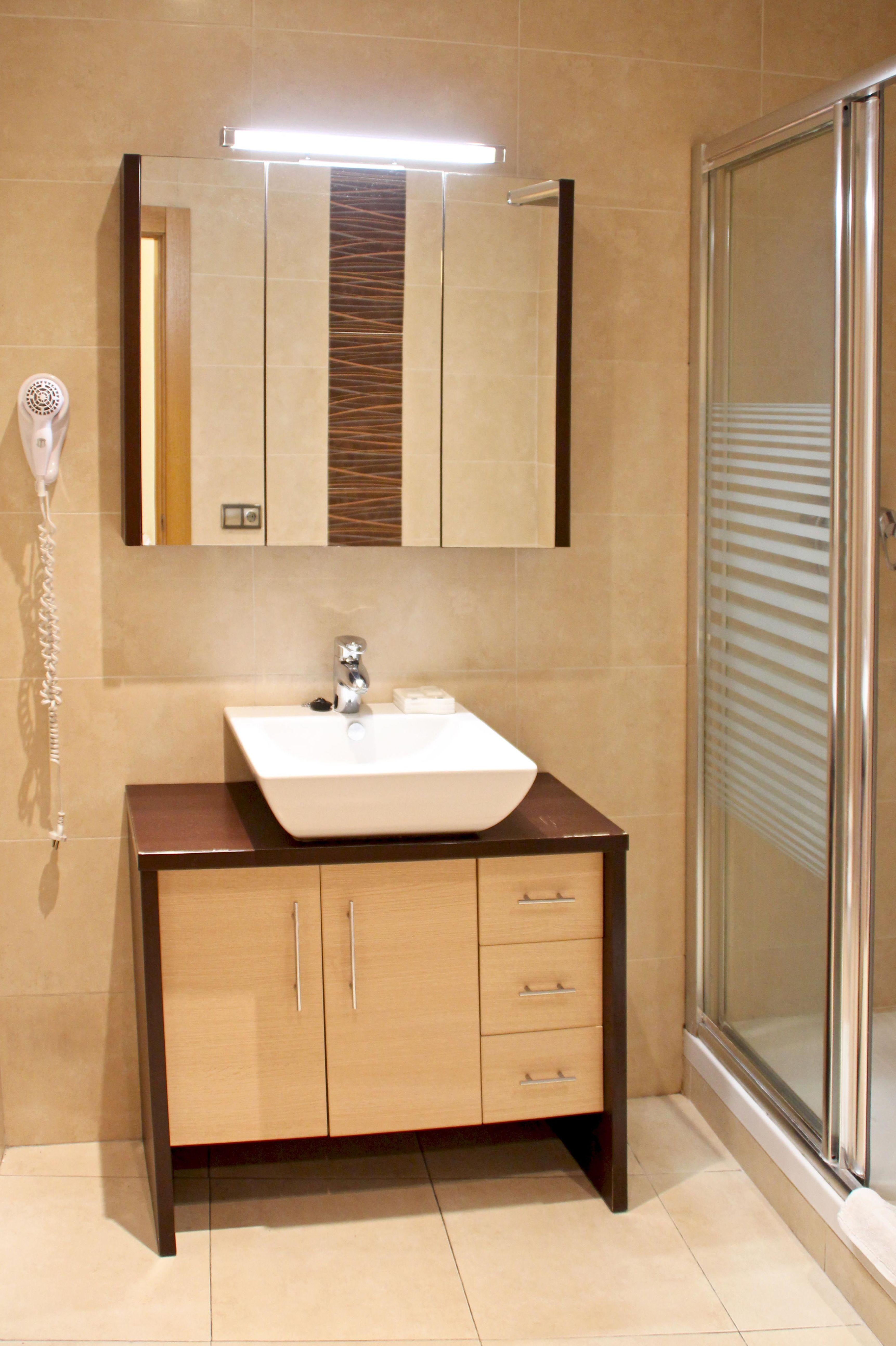 Baño ensuite con ducha, amenities y secador de pelo