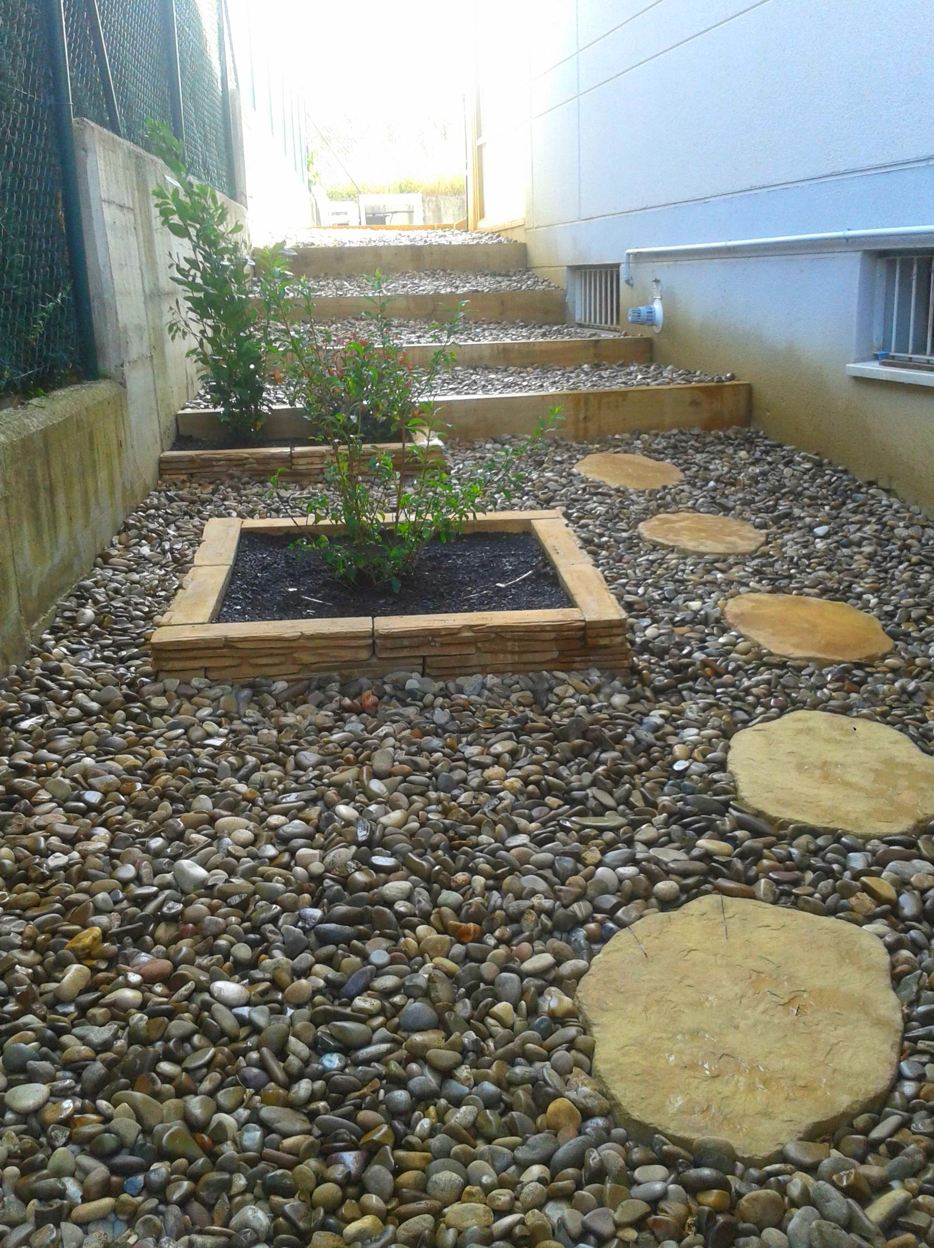 Paso lateral camino jardineras escaleras madera aridos canto rodado
