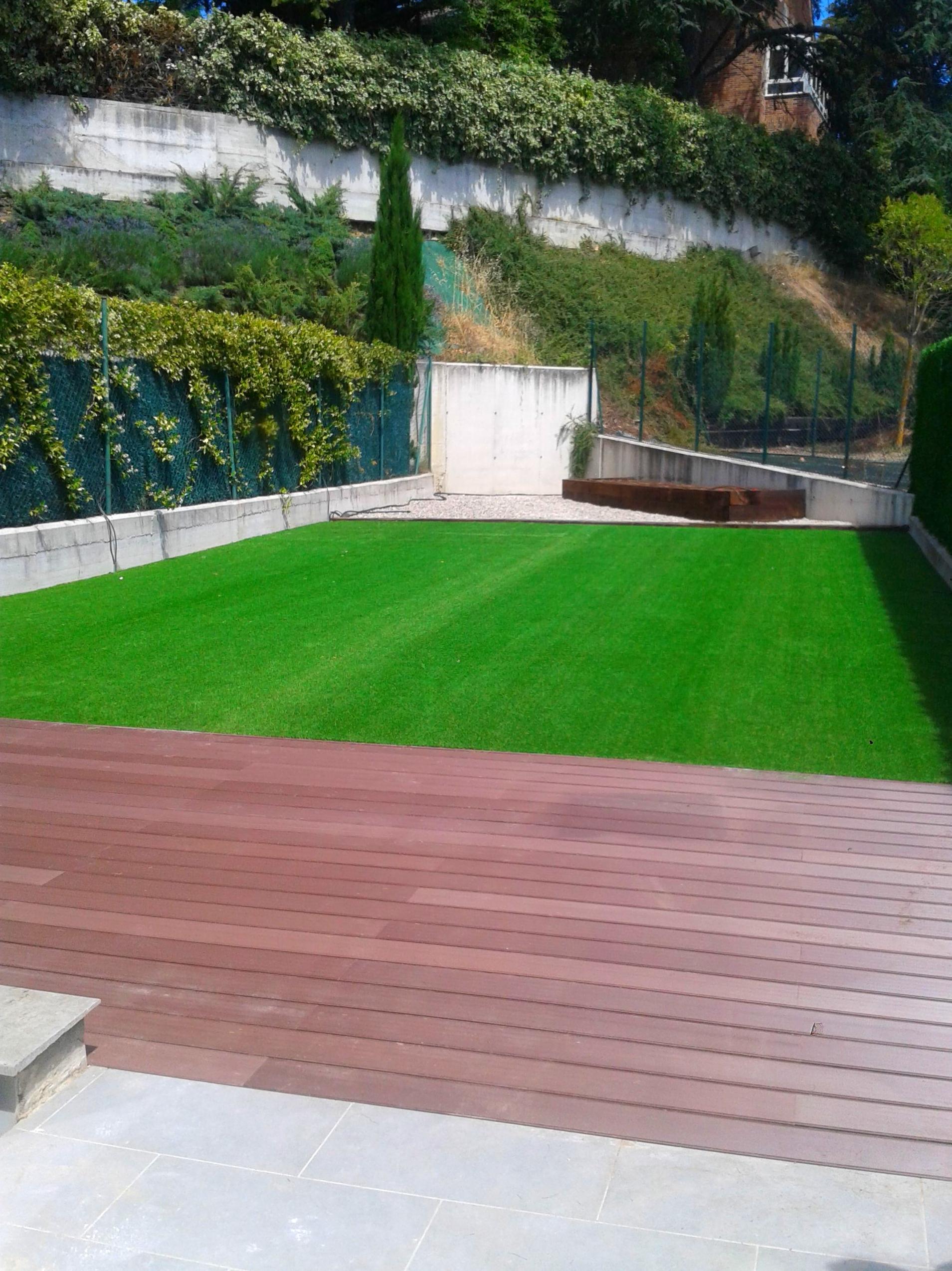 Jardín con césped artificial, tarima de madera, áridos y bancal para huerta.
