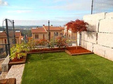 Jardín con césped articicial y madera