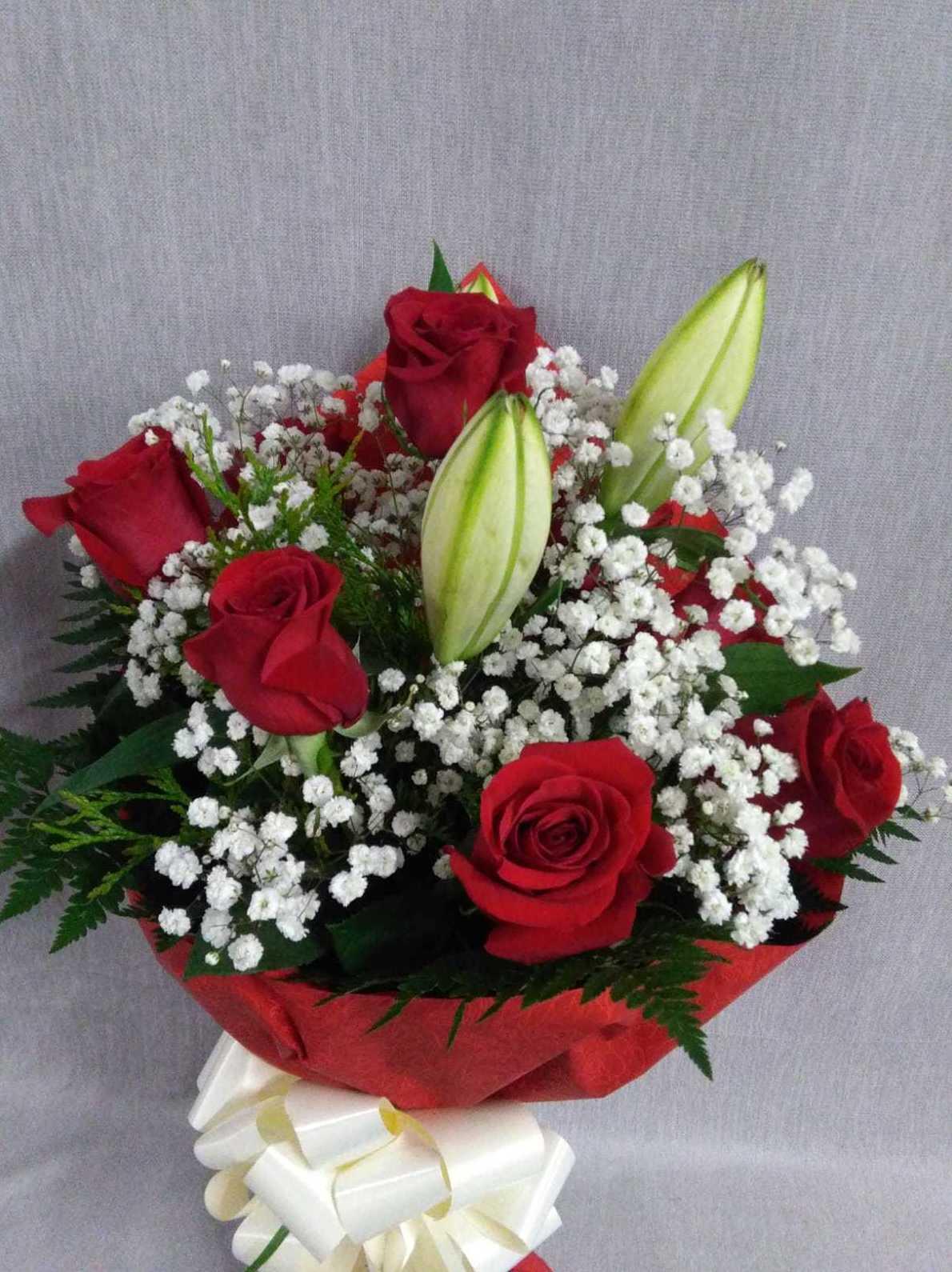 6 rosas rojas y un lilium blanco cerrado