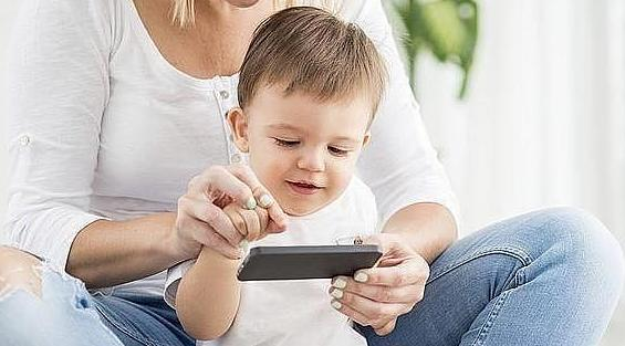 Un niño aprende a manejar un móvil