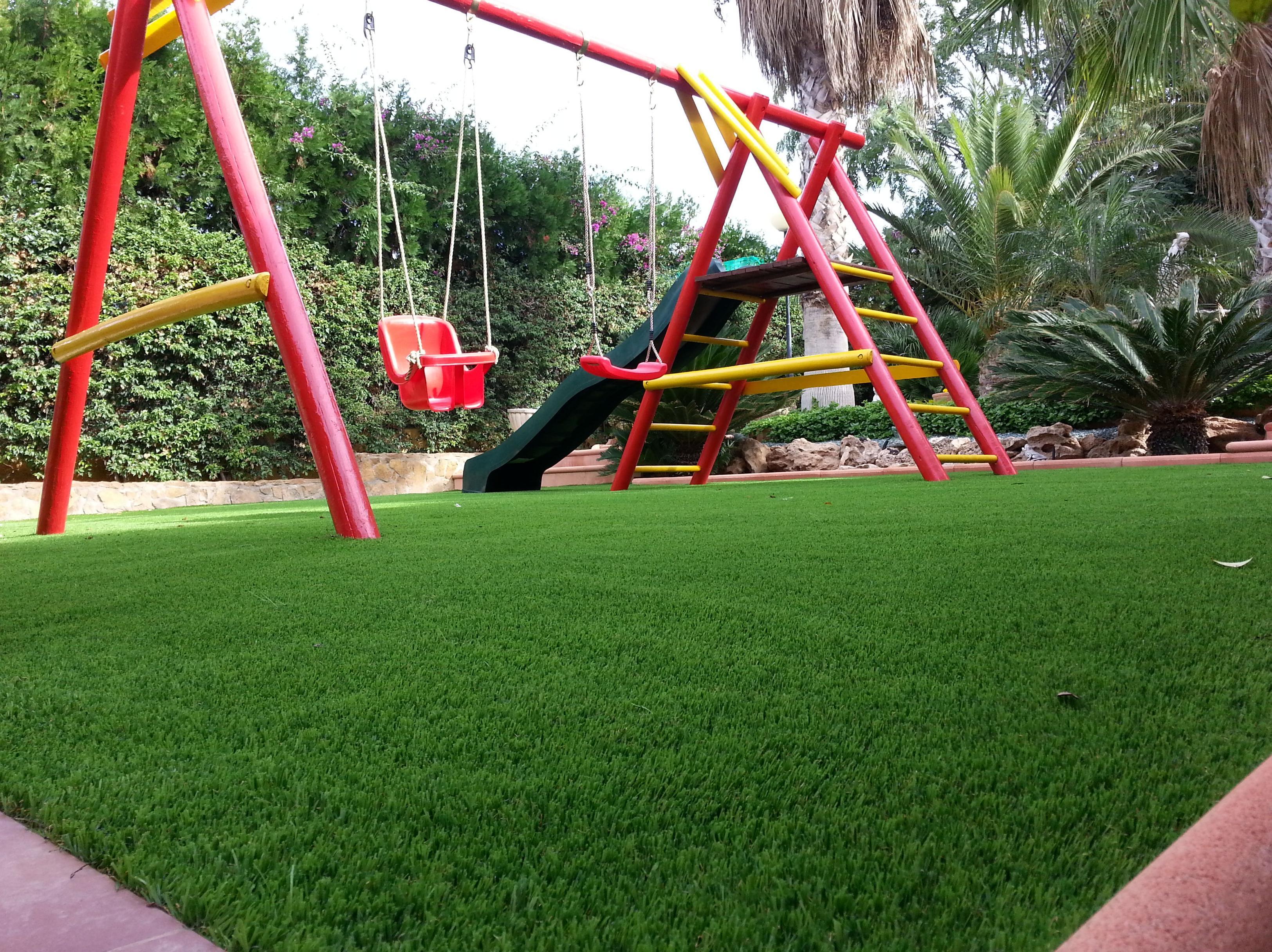 Jardin particular después del montaje con césped artificial y zona juegos, columpio en Valencia