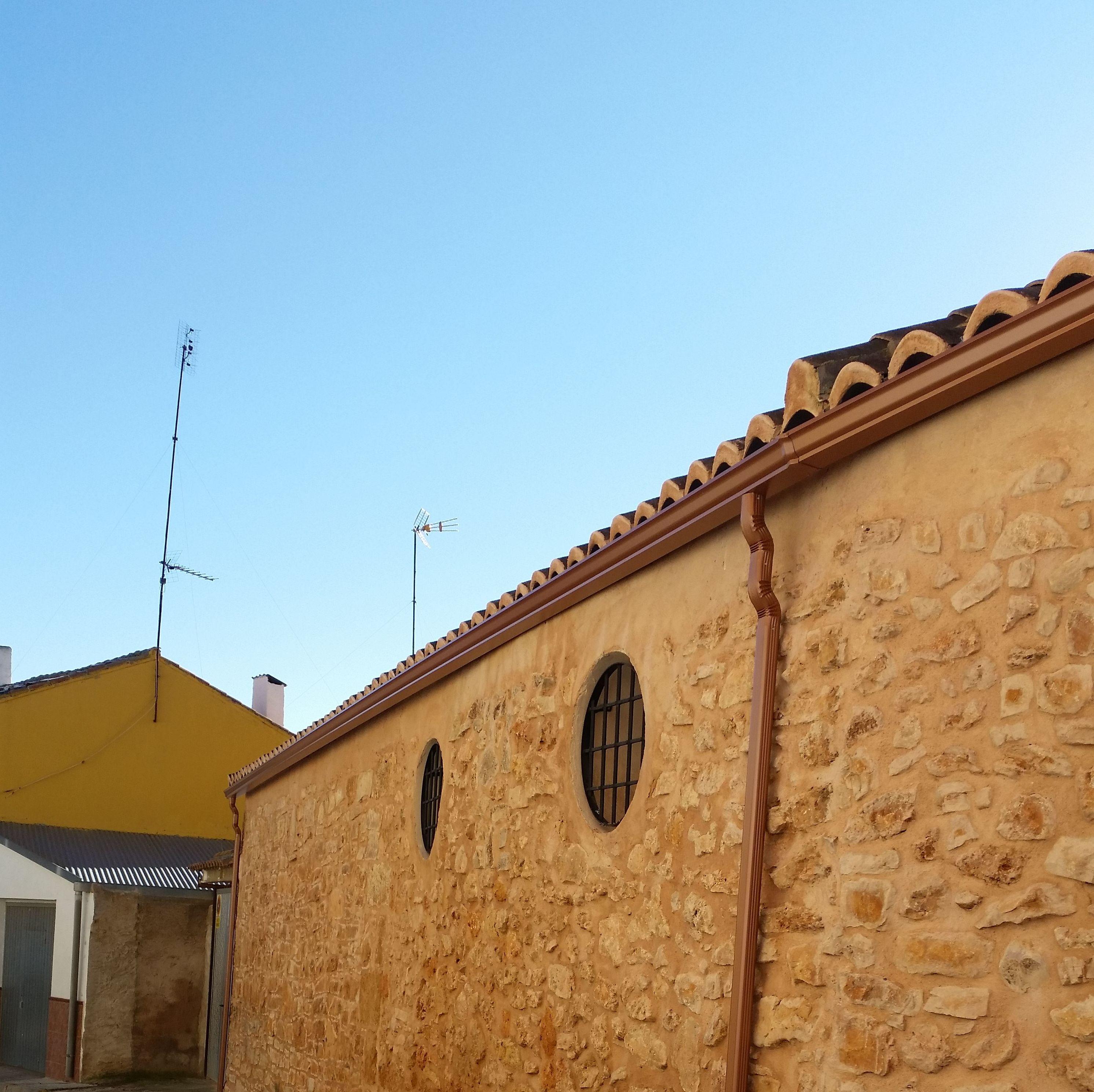 canalo de aluminio en color cobre para fachada rústica de piedra
