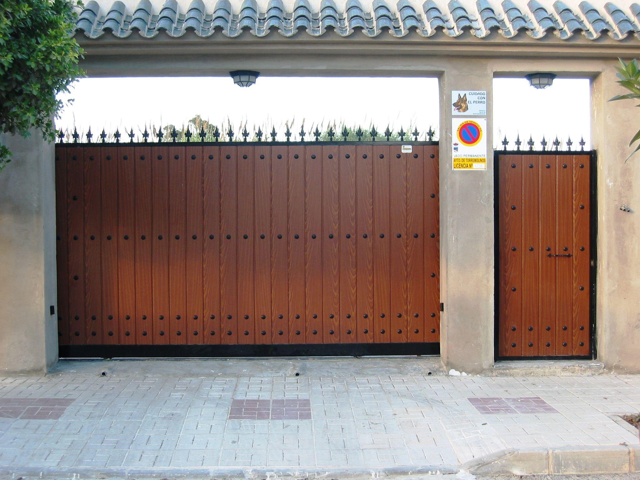 Puerta corredera y abatible de madera con clavos y lanzas