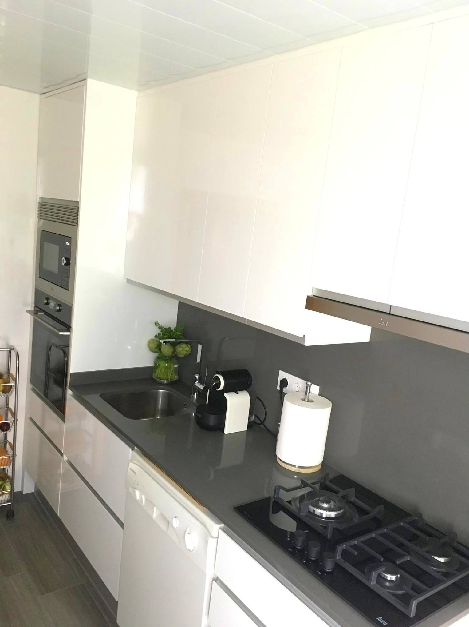 Reforma de cocina en formica blanco brillo y tirador uñero de aluminio.