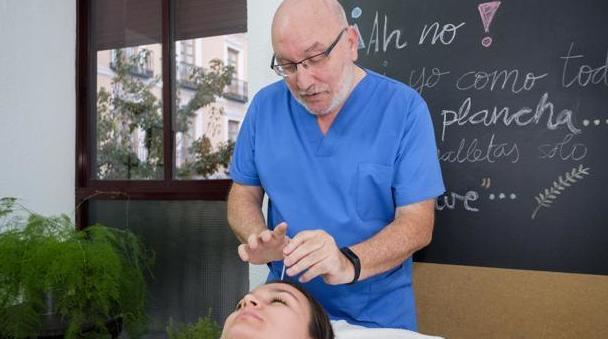 especialista en medicina tradicional china, coloca una aguja en una paciente