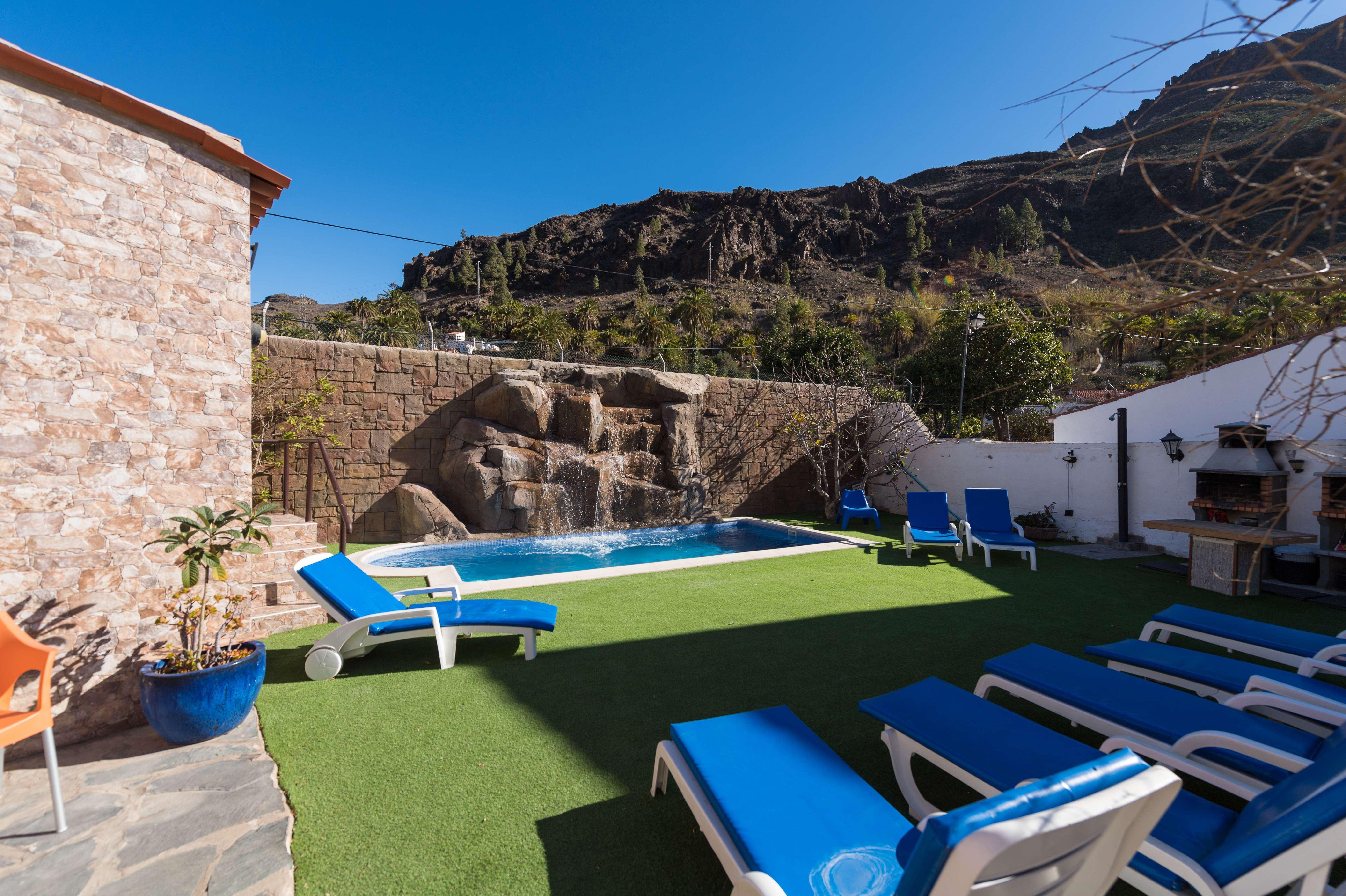 La casa cuenta con un jardín con piscina y zona de barbacoa