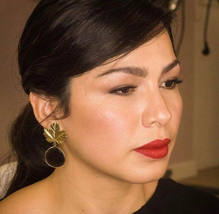 Coleta baja despeinada con ondas y una piel luminosa combinada con un labial rojo para un look de invitada perfecto