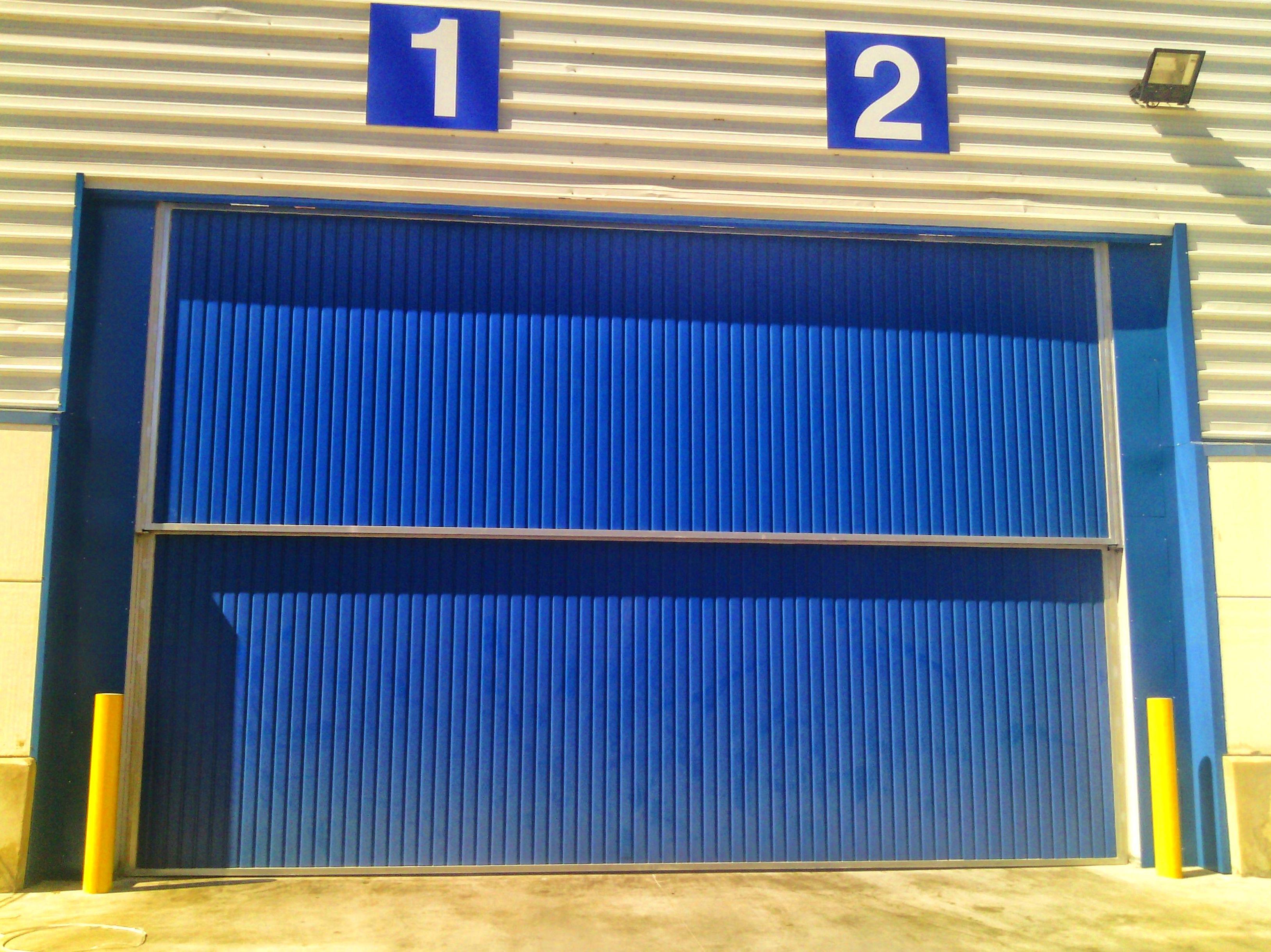Puerta industrial guillotina de chapa grecada vertical de 2 hojas