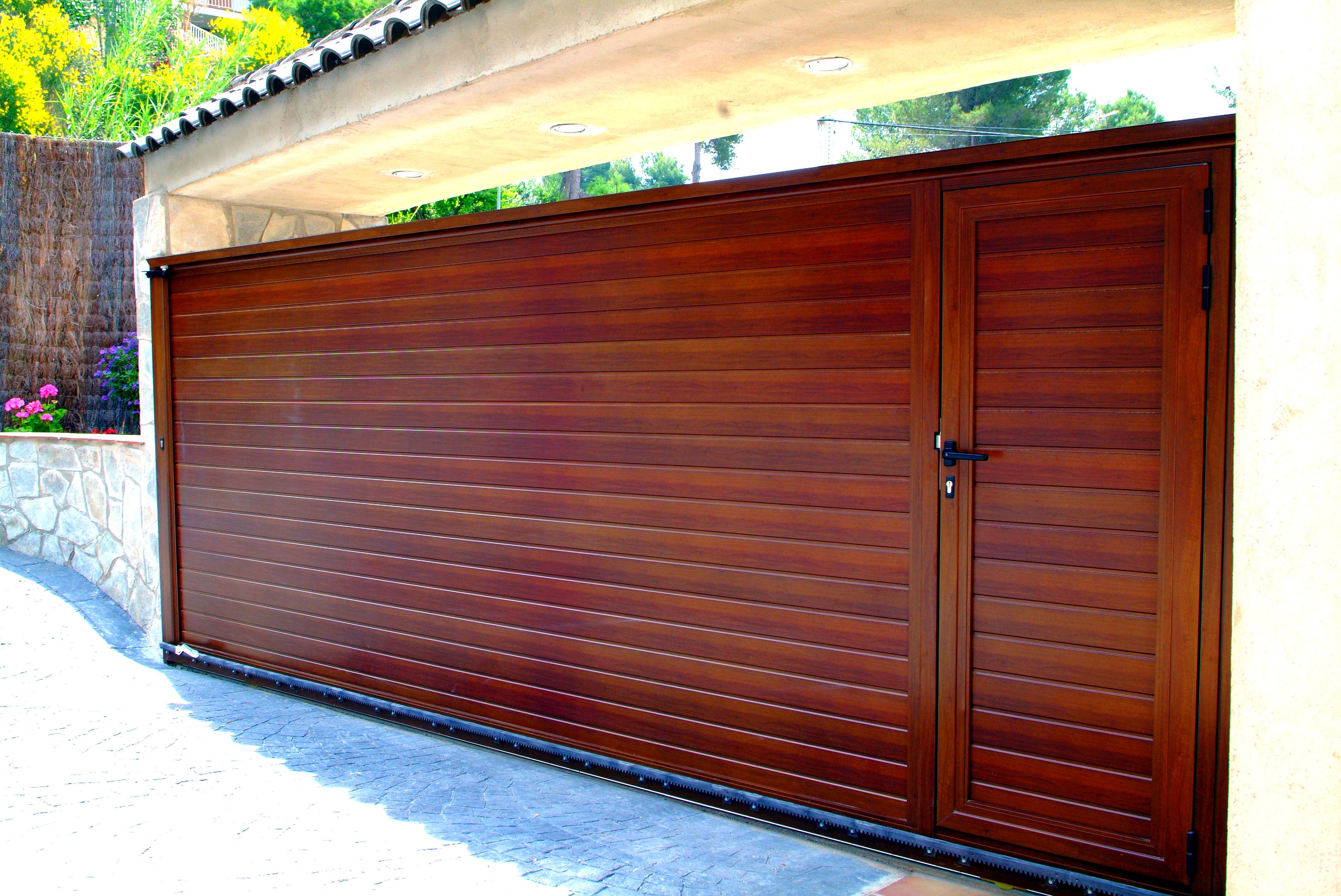 Puerta corredera de aluminio imitación madera con puerta peatonal incorporada
