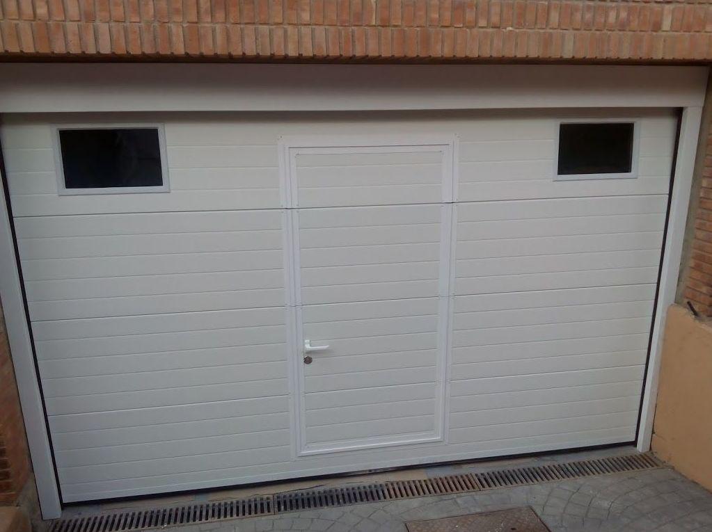 Puerta seccional de panel de 40mm acanalado blanco con puerta peatonal y mirillas