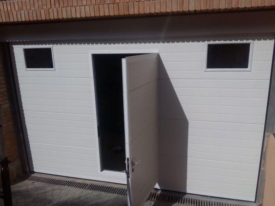 Puerta seccional de panel acanalado con puerta peatonal incorporada
