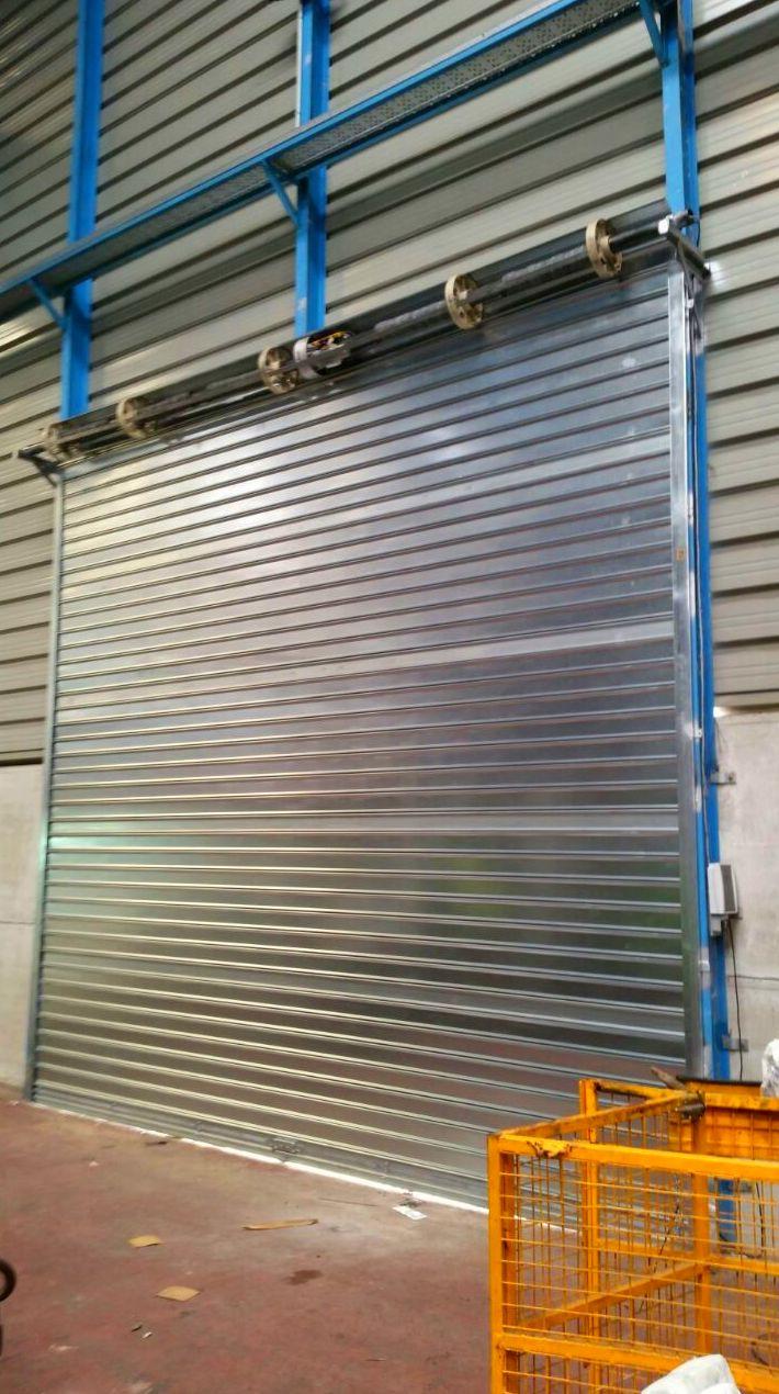 Puerta enrollable metálica industrial automática de apertura hombre presente