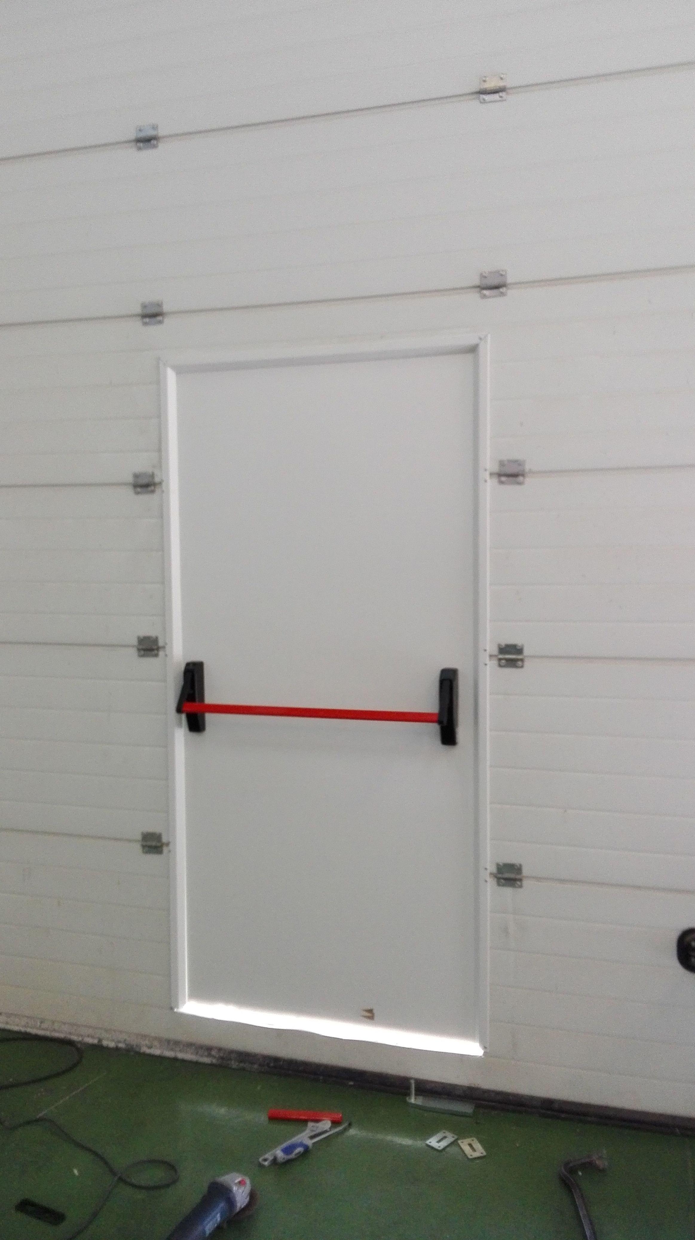 Montaje de Puerta peatonal en puerta seccional apertura vertical de guillotina