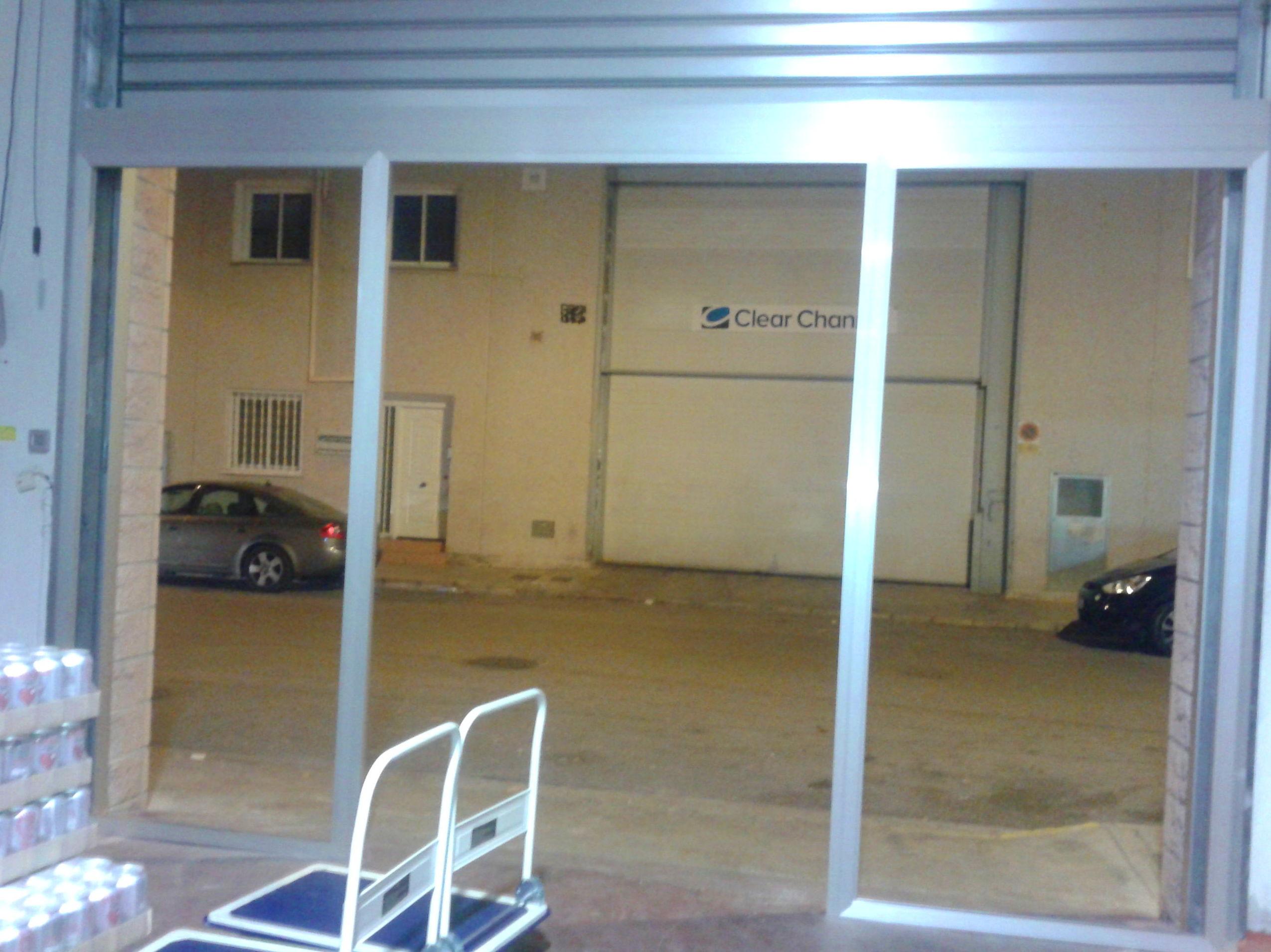 Frente de aluminio plata y puerta metálica enrollable