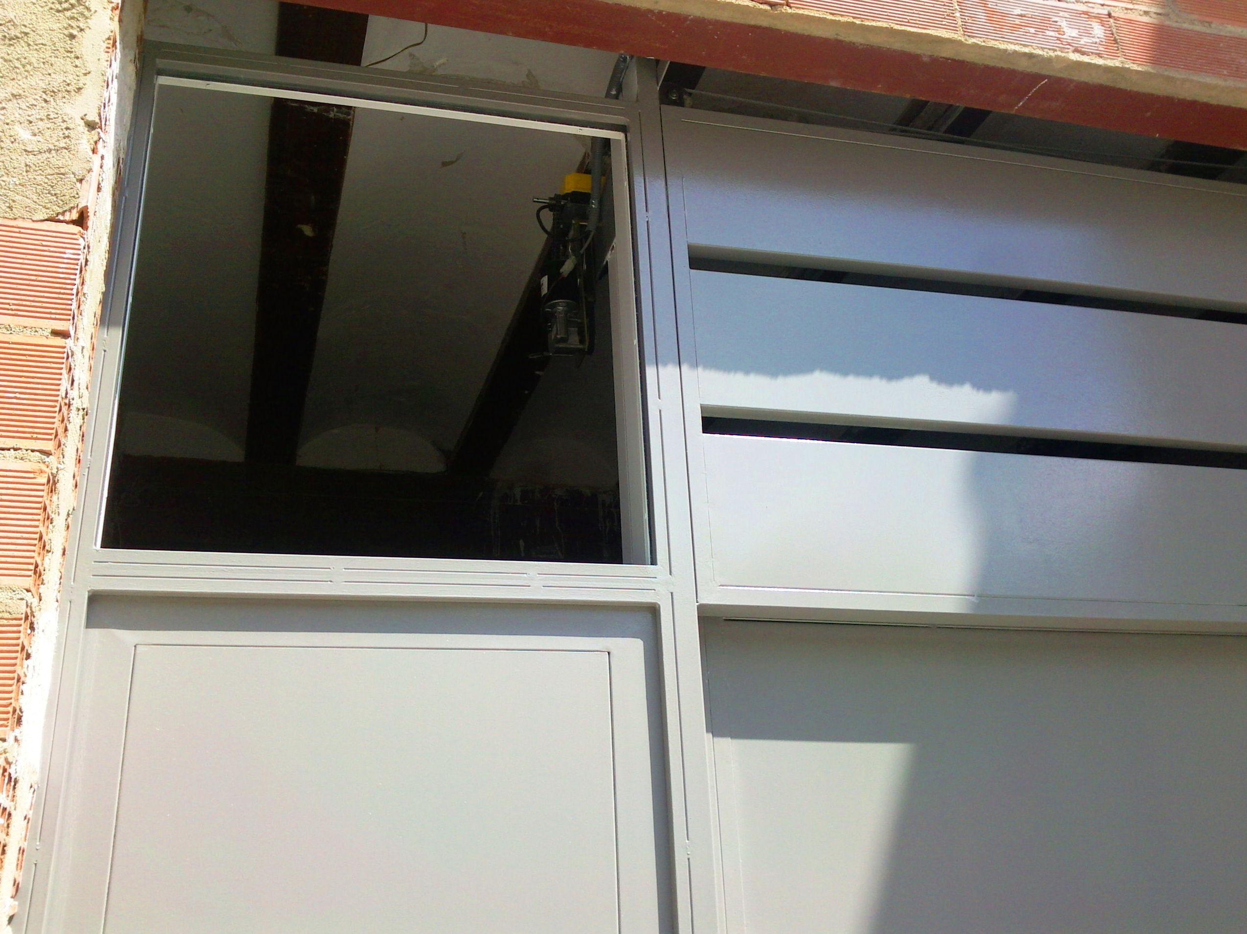 Puerta guillotina de 2 hojas con peatonal y fijo superior lacada al horno