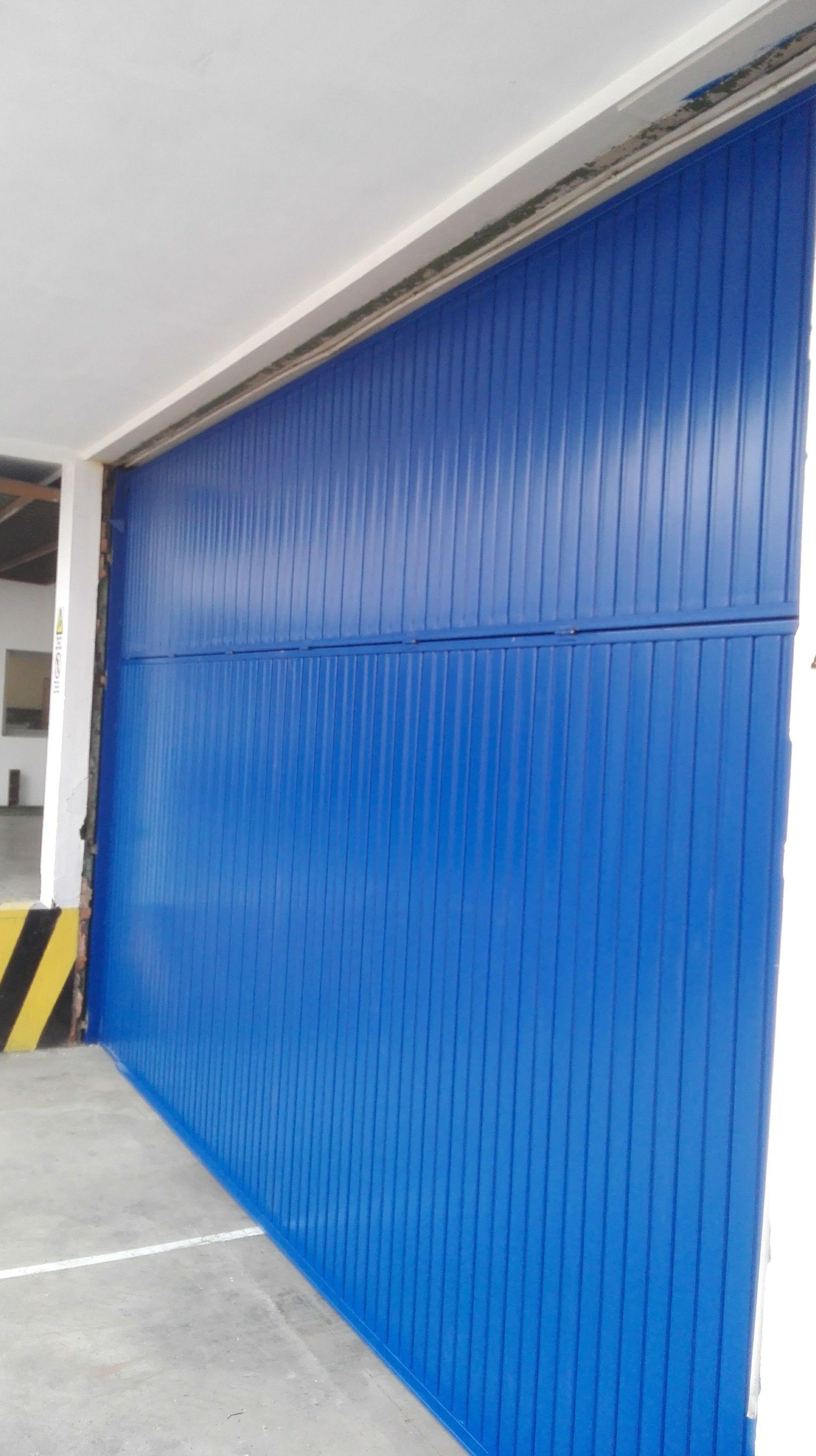 Puerta basculante de contrapesos de chapa metálica en pintura de color azul 5005 en Paterna