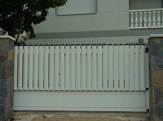 Puerta Corredera de aluminio con barrotes y zócalo lamas lisas