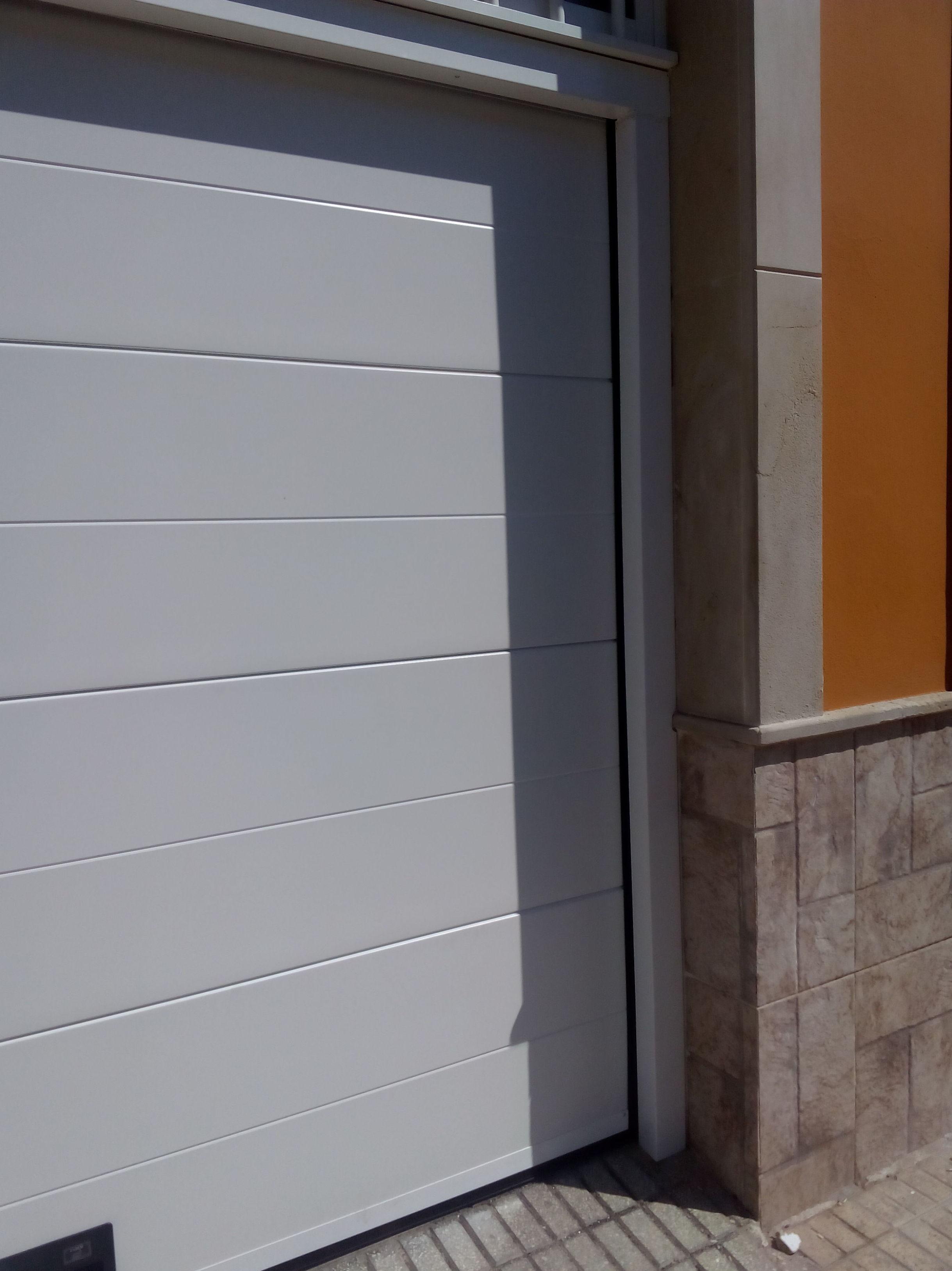 Puerta seccional automática panel liso y forro de marco mismo color