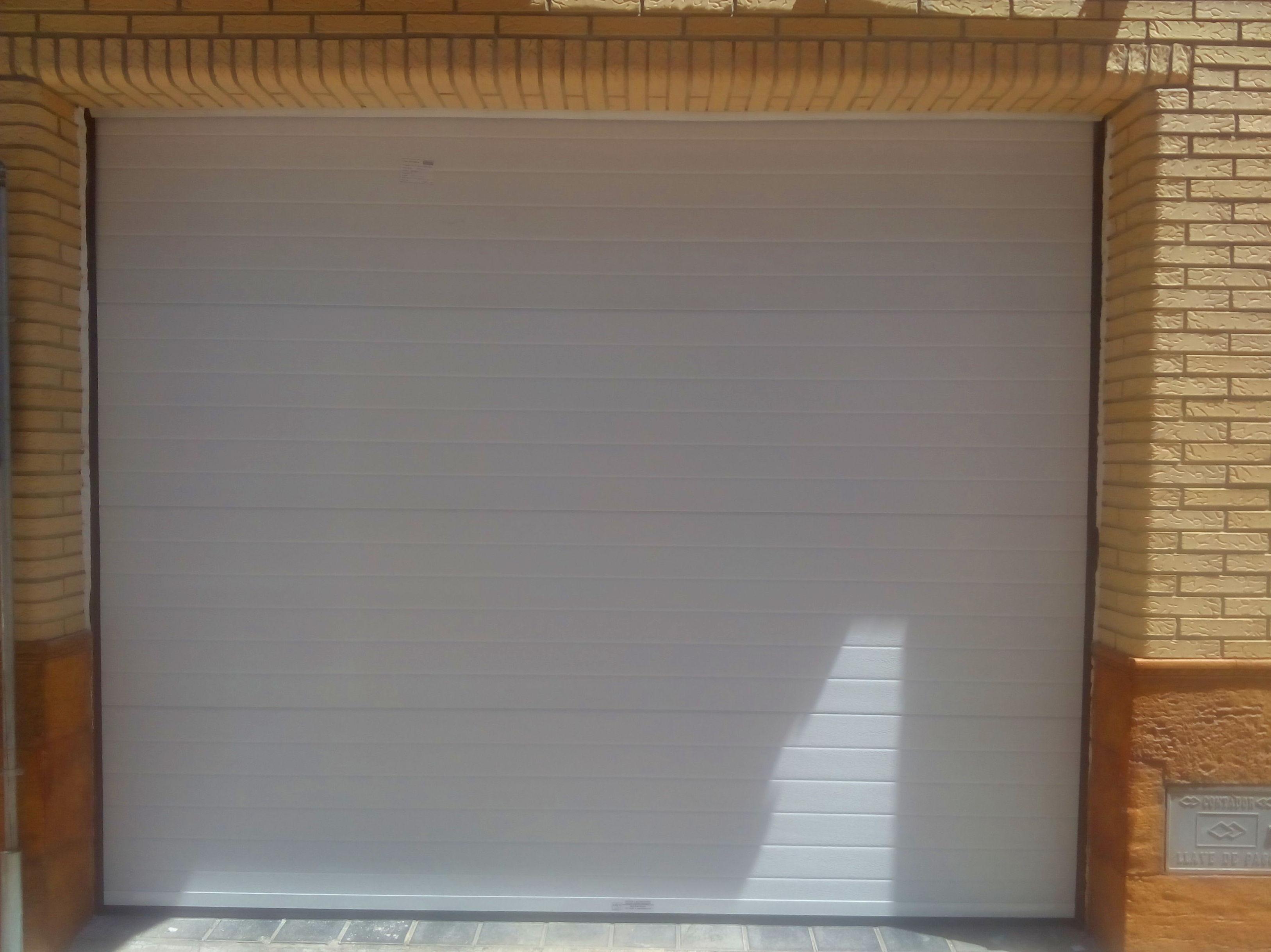 Puerta Seccional gofrada blanca. montada sobre pared sin premarco ( vista exterior )