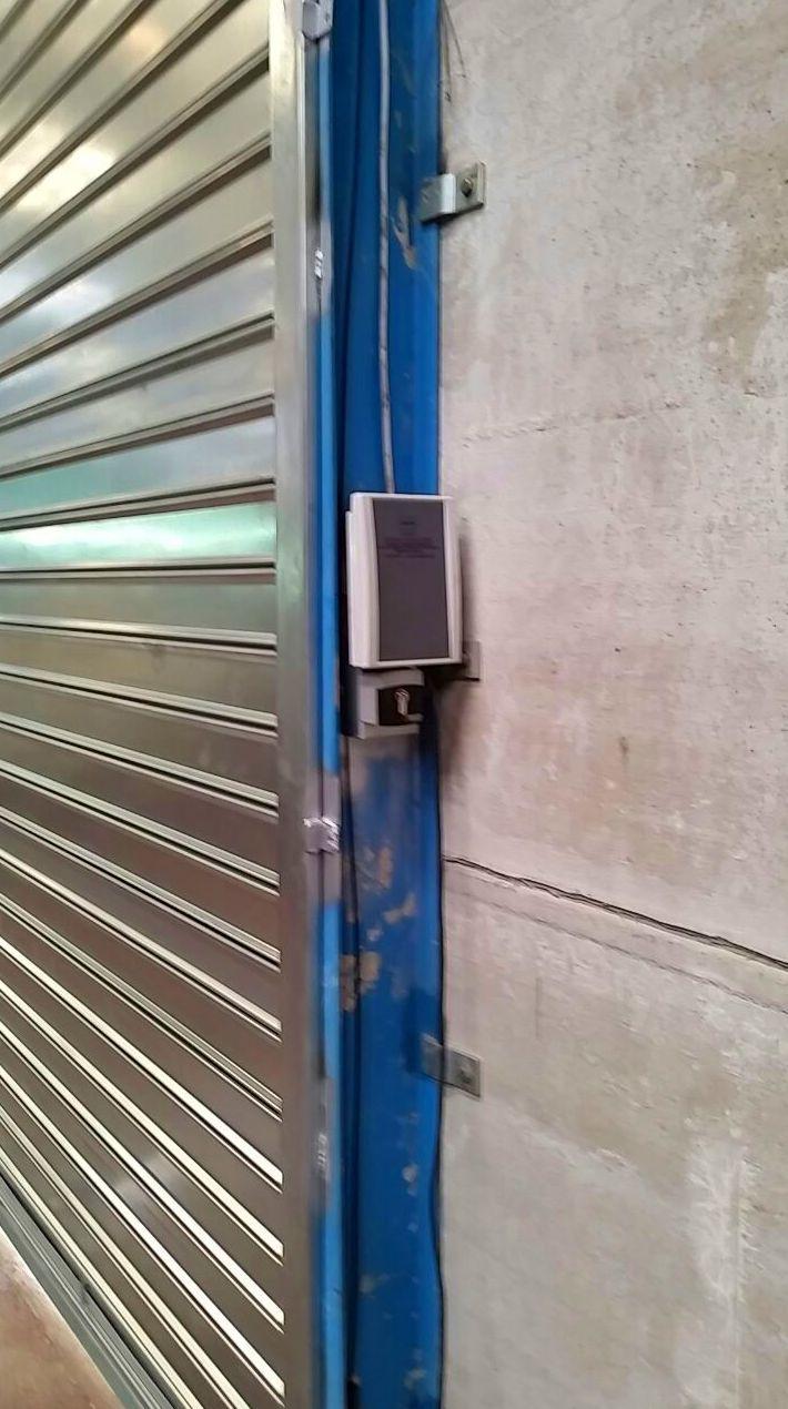 Puerta enrollable industrial automática de apertura hombre presente