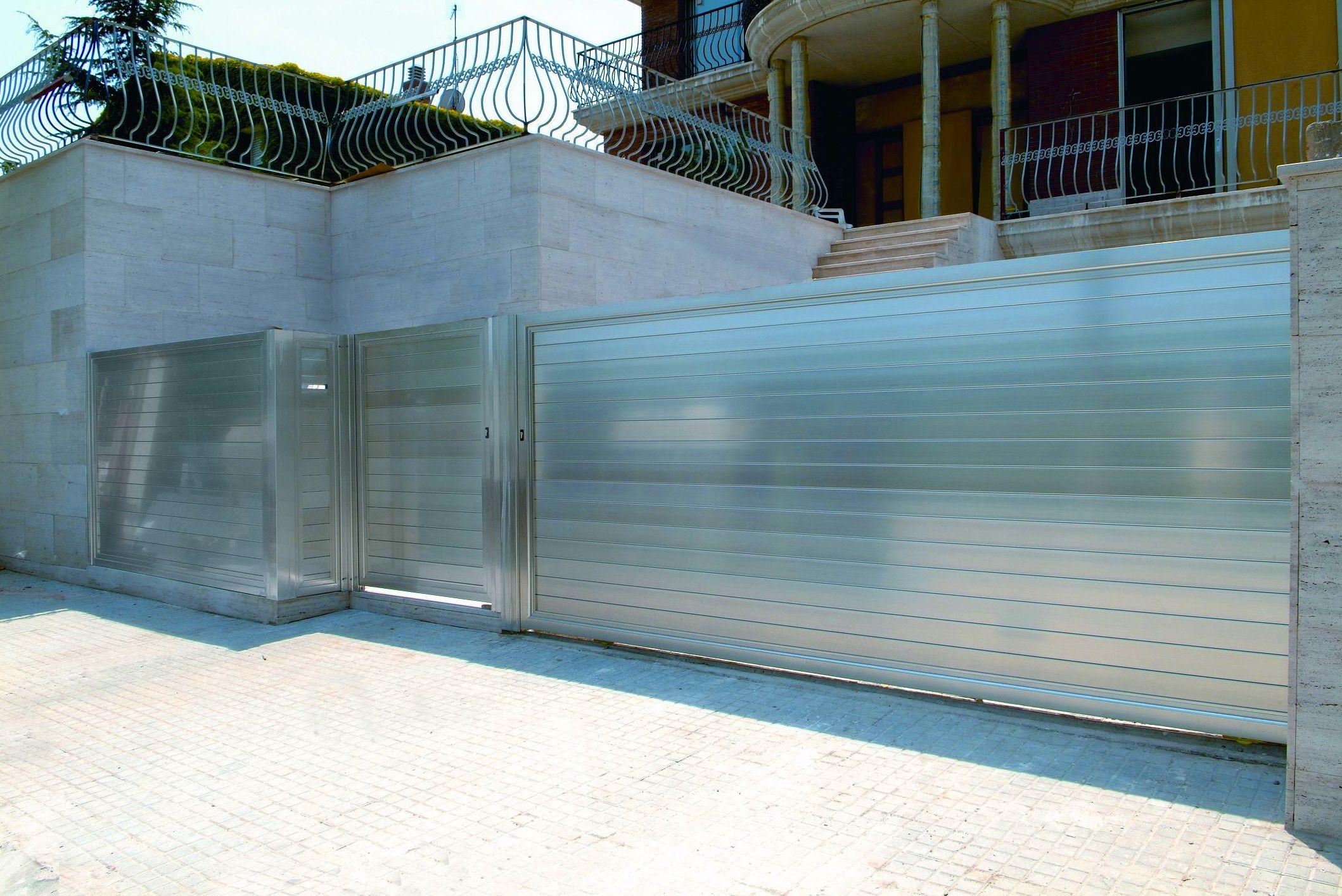 puerta corredera de aluminio en plata anodizado brillo inoxidable con puerta peatonal y valla
