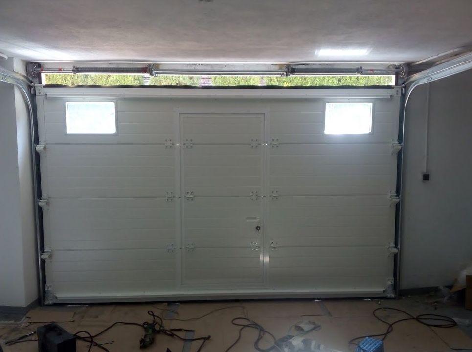 Puerta seccional con puerta peatonal de panel gofrado blanco y mirillas