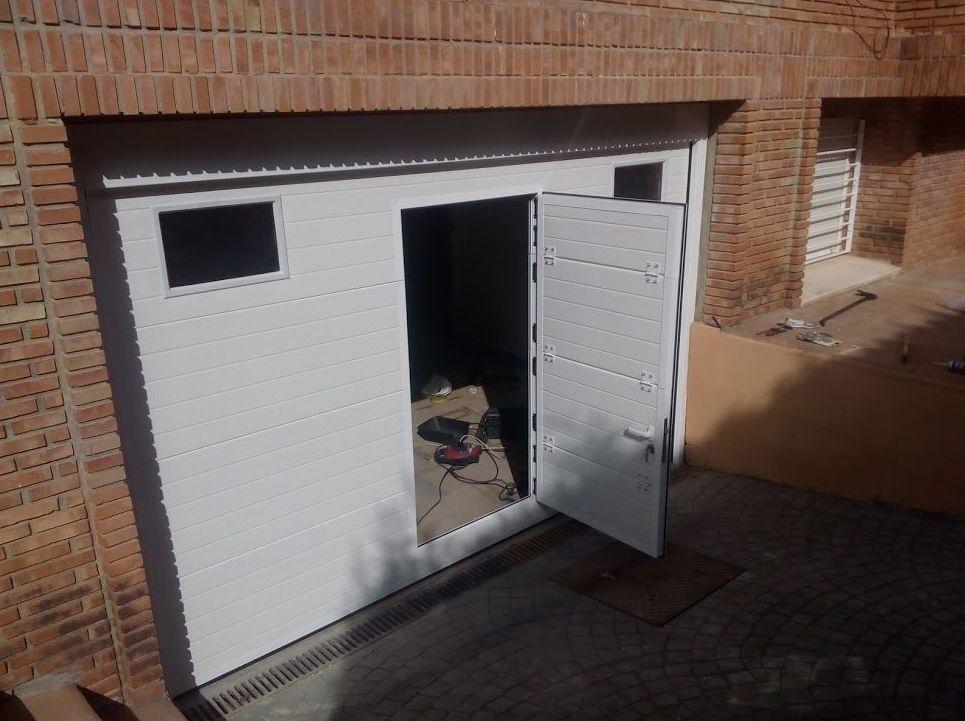 Puerta seccional con puerta peatonal incorporada de panel acanalado