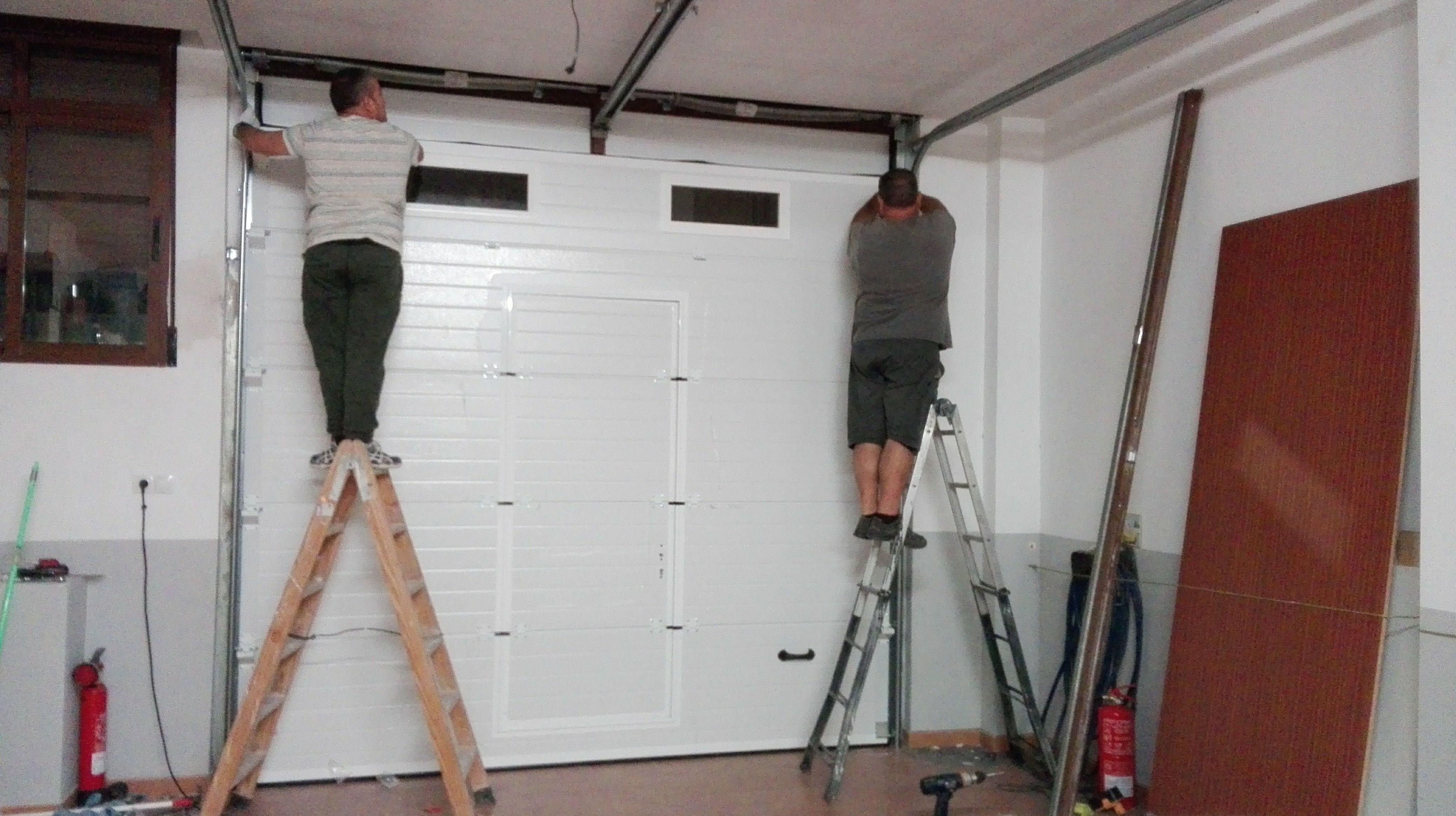 Puerta seccional con puerta peatonal de panel blanco y mirillas