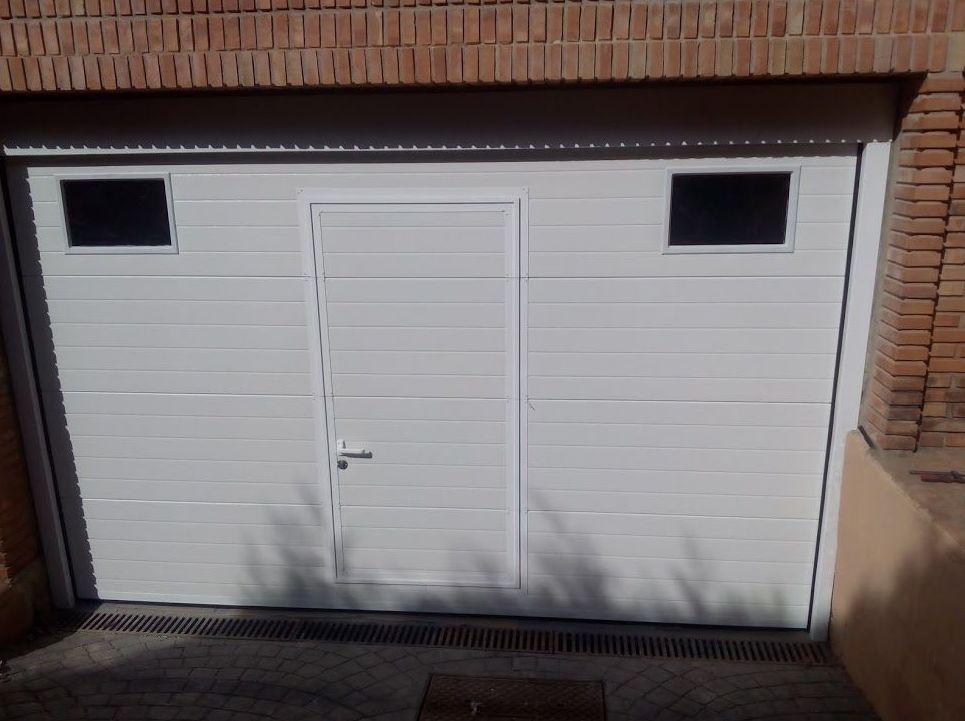 Puerta seccional y puerta peatonal inscrita de panel acanalado blanco y mirillas