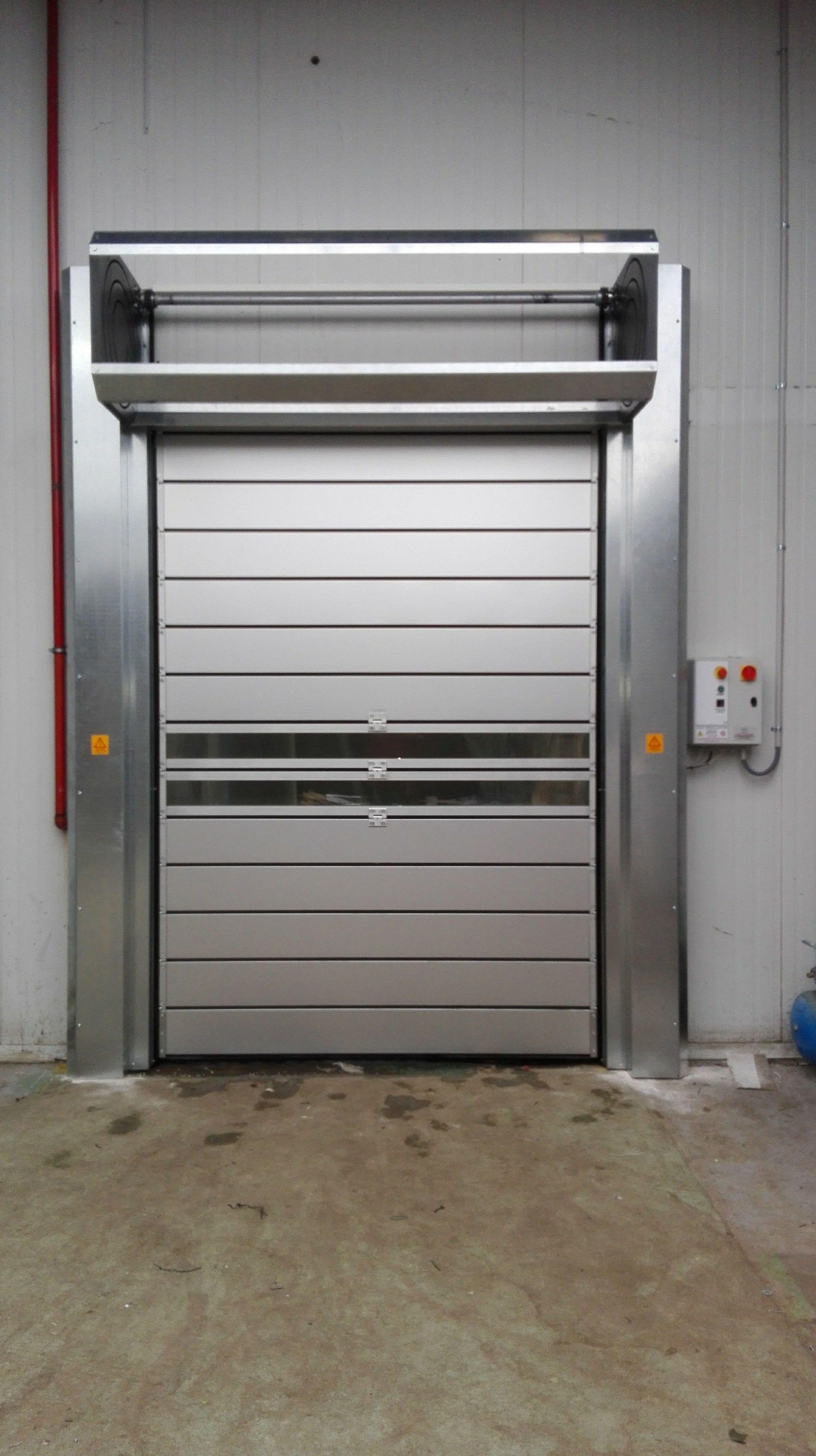 Puerta muy rápida para alimentación de paneles térmicos enrollables en espiral.