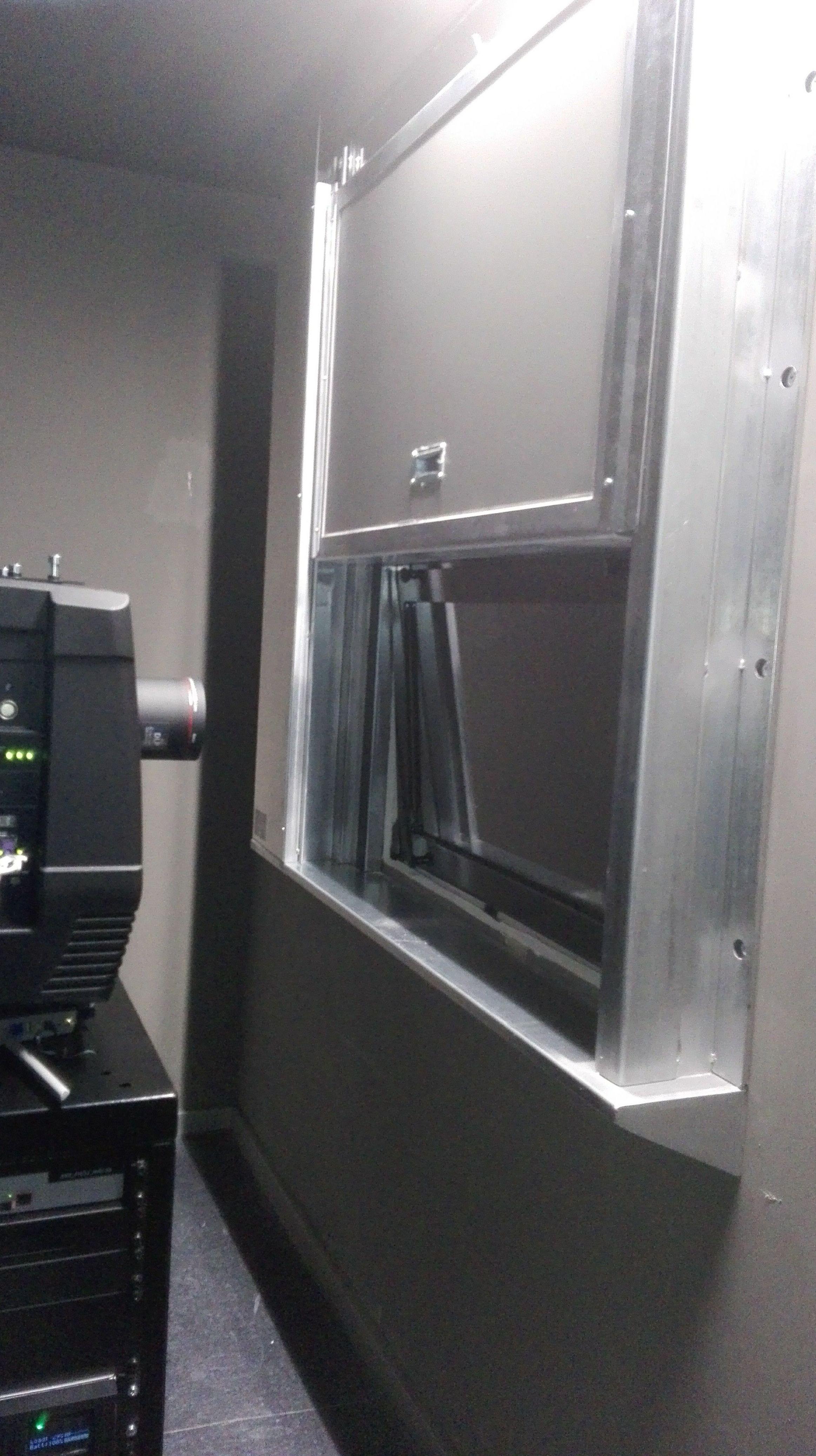 Puerta guillotina en Ventana cortafuegos sala de cine, sujeción a tabique de yeso