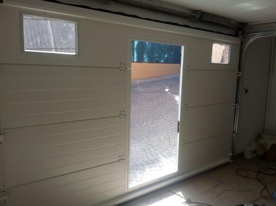 Puerta seccional y puerta peatonal inscrita de panel