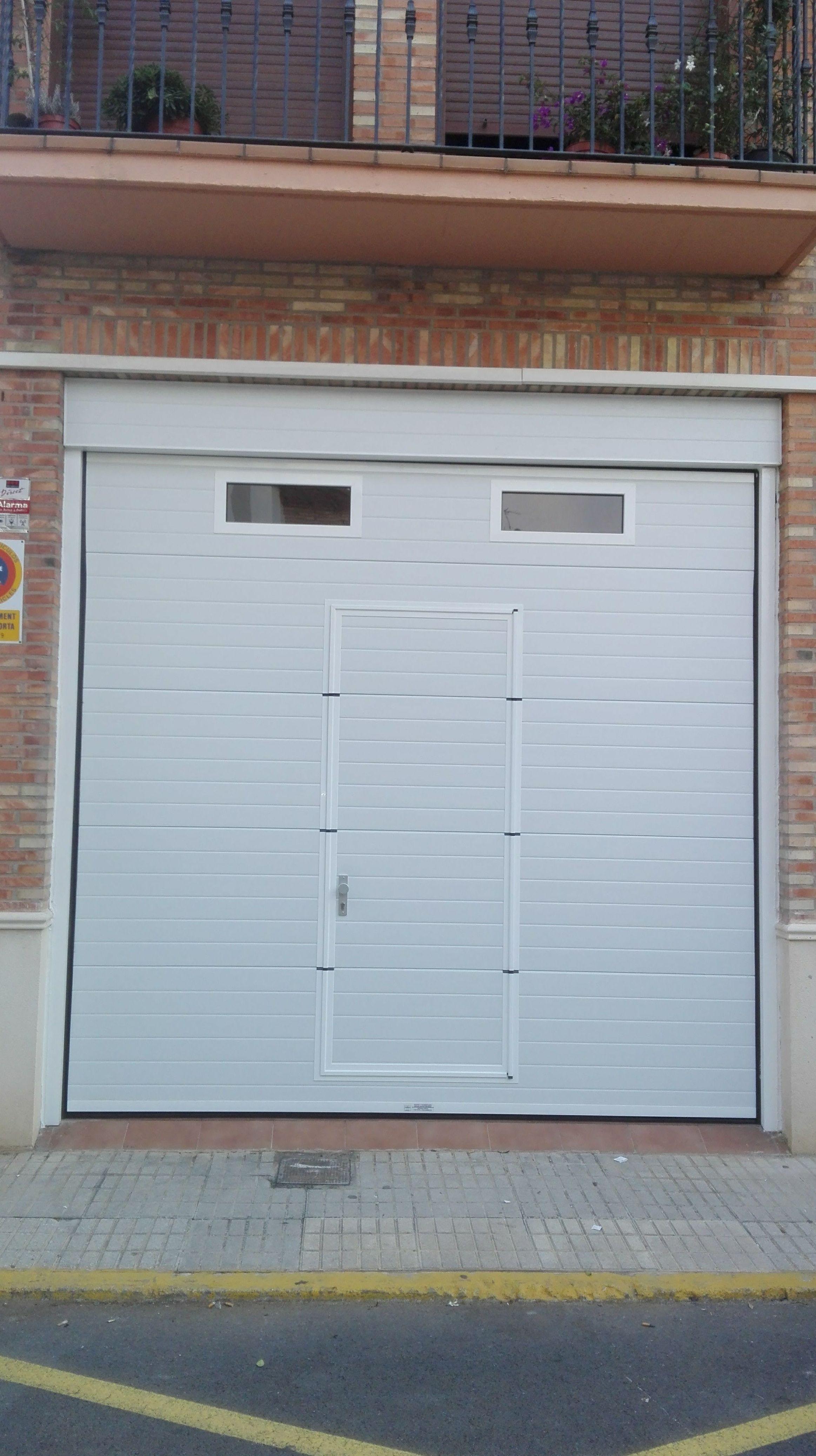 Puerta seccional con puerta peatonal y fijo de panel acanalado blanco y mirillas
