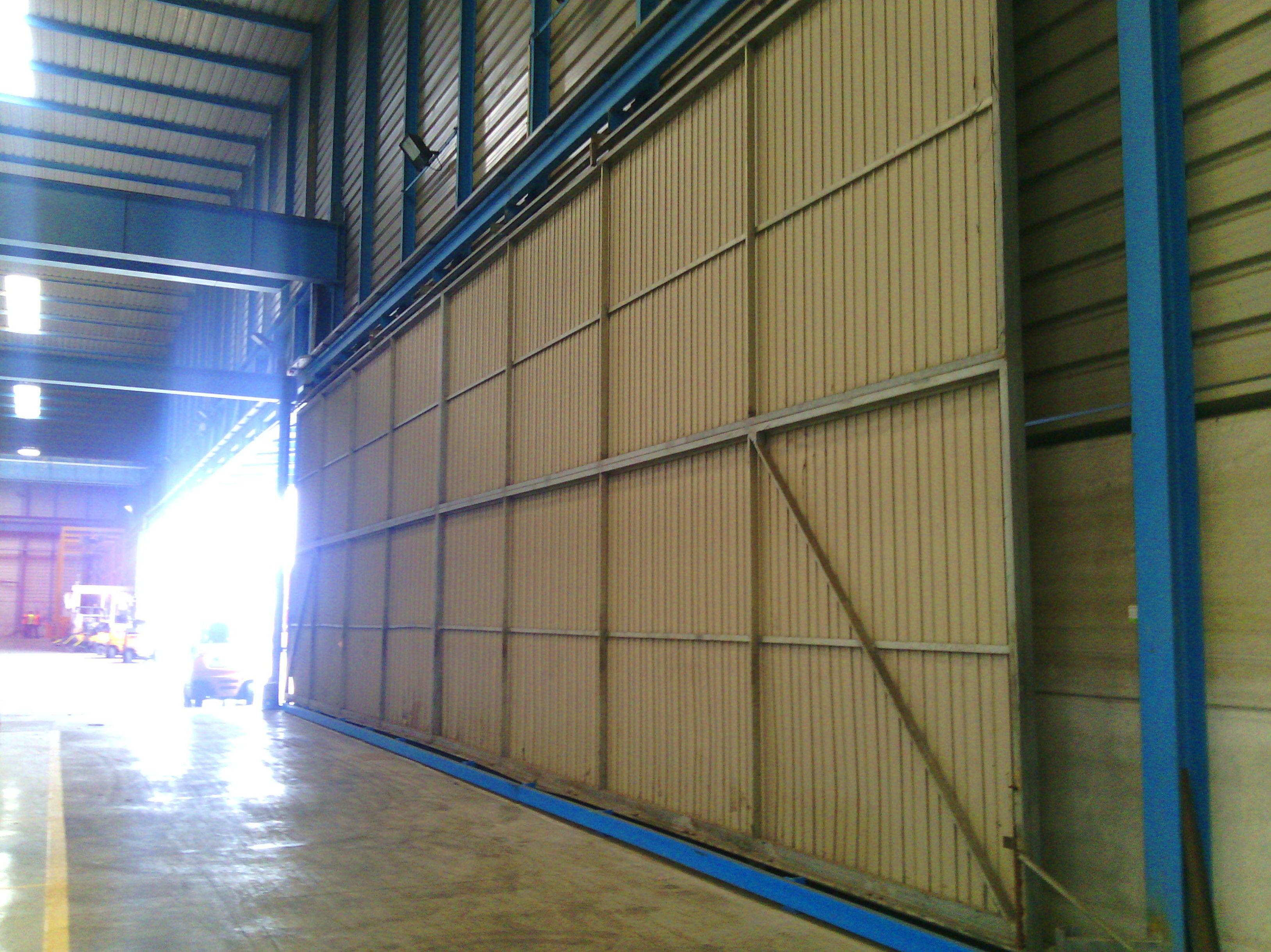 Puerta corredera Metálica industrial con guías aéreas suspendidas de 20 metros