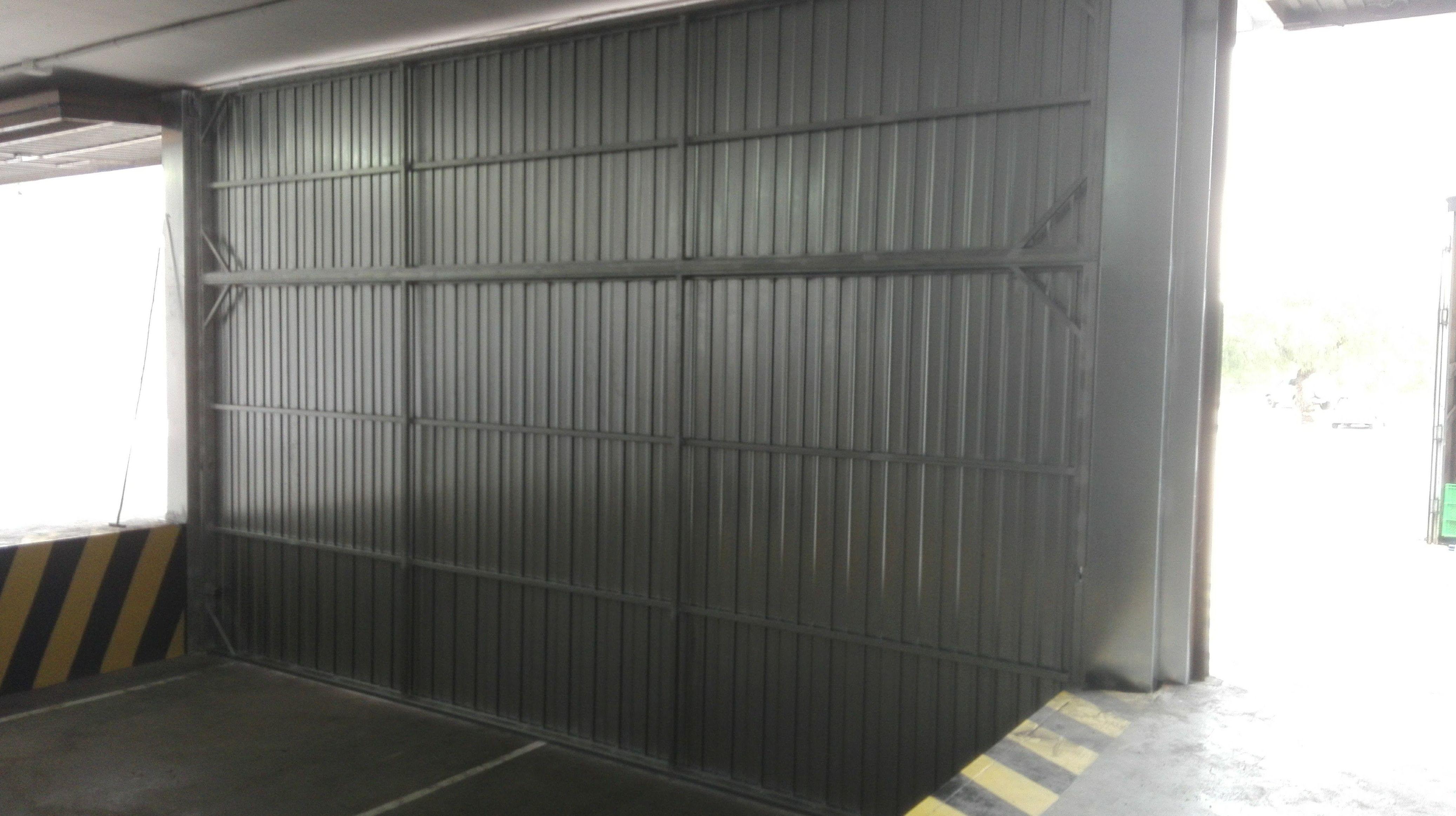 Puerta basculante de contrapesos industrial chapa galvanizada parte interior en Paterna