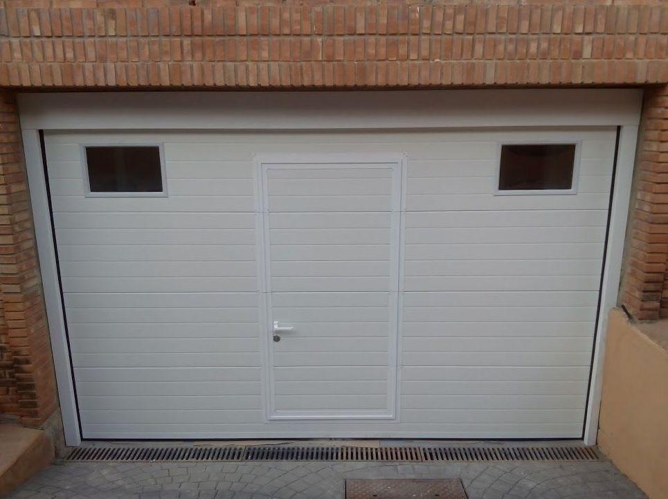 Puerta seccional de panel acanalado con marcos forrados en chapa mismo color
