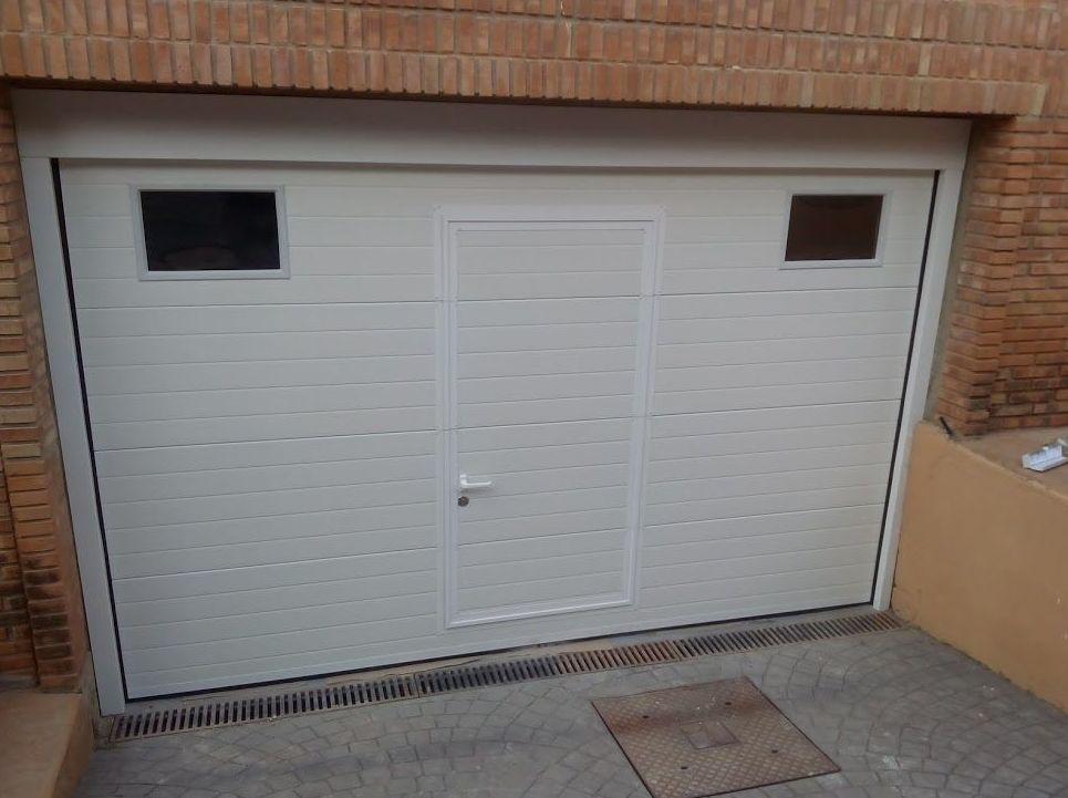 Puerta seccional con puerta peatonal de panel acanalado blanco y mirillas