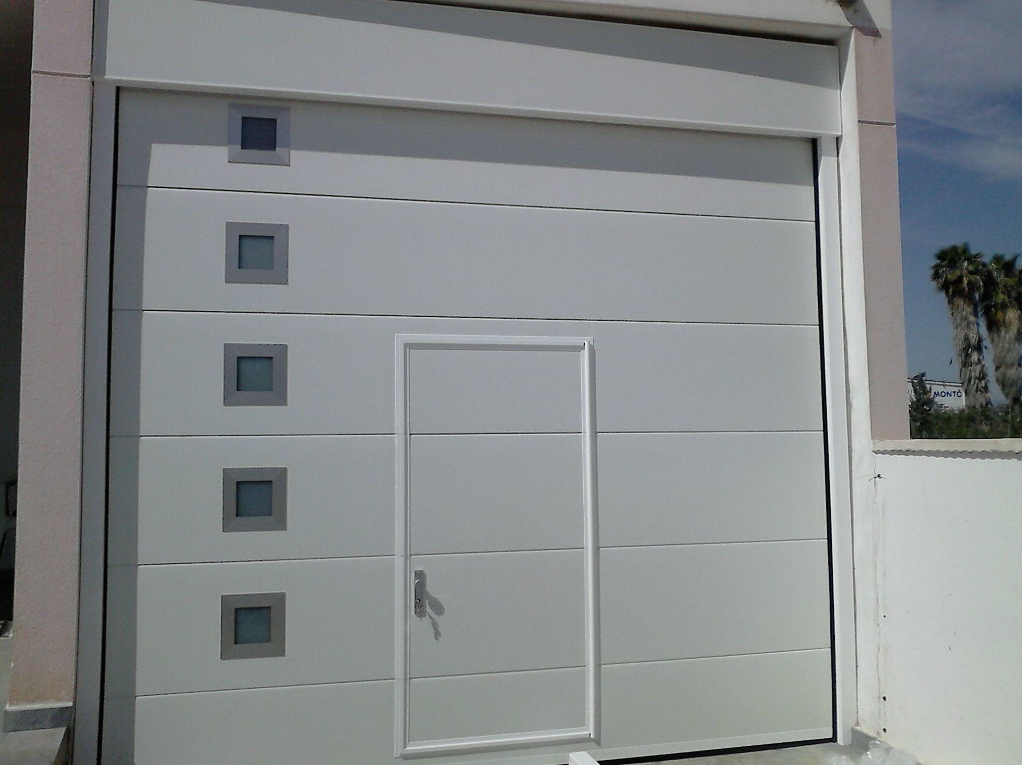 Seccional panel canal liso blanco con ventanas fijas laterales y portón peatonal.