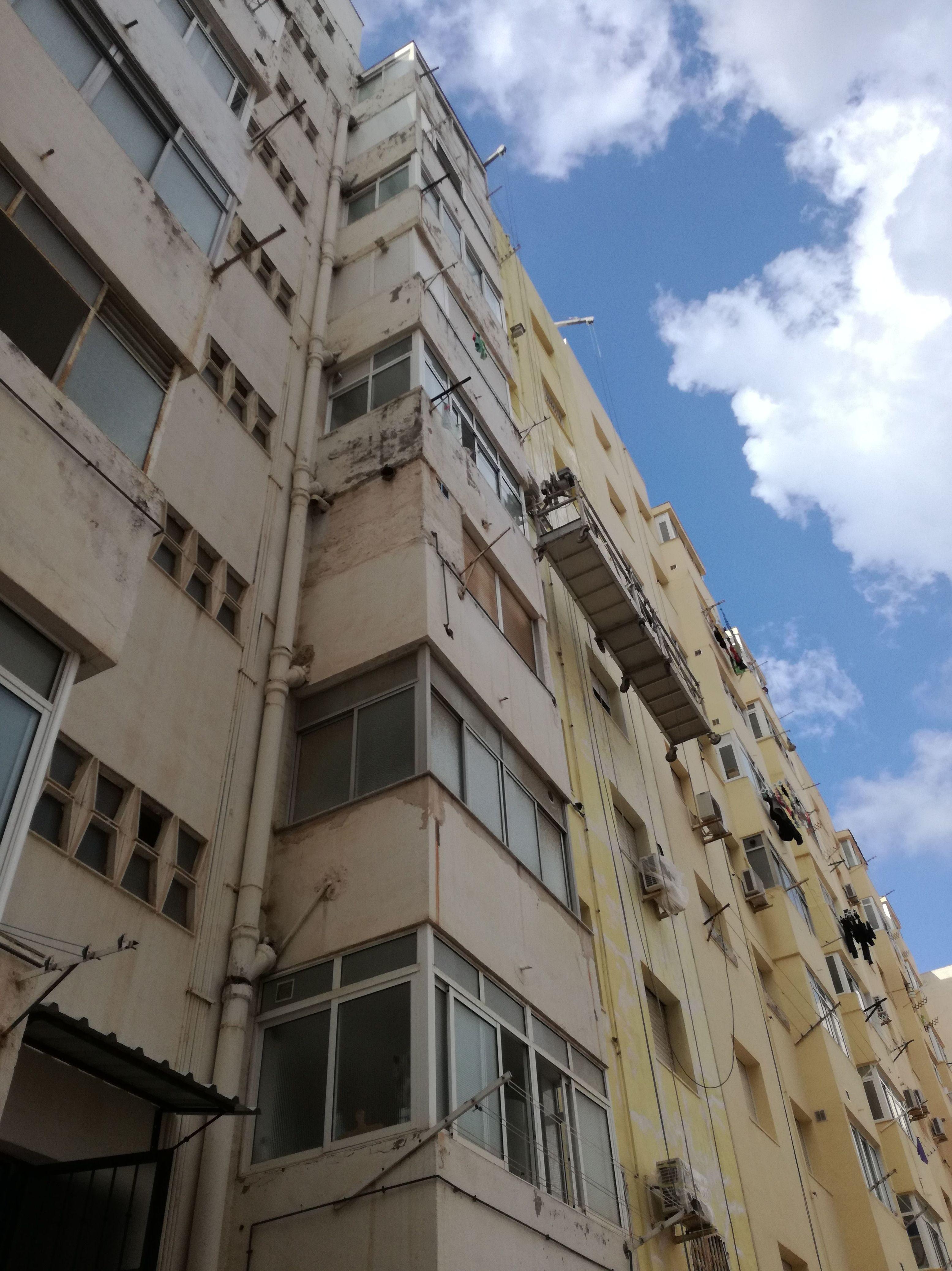 Rehabilitación de fachada con patologías superficiales en una Cdad. de Prop. de Sector Estación de Cartagena. Con andamios colgados sobre pescantes en azotea