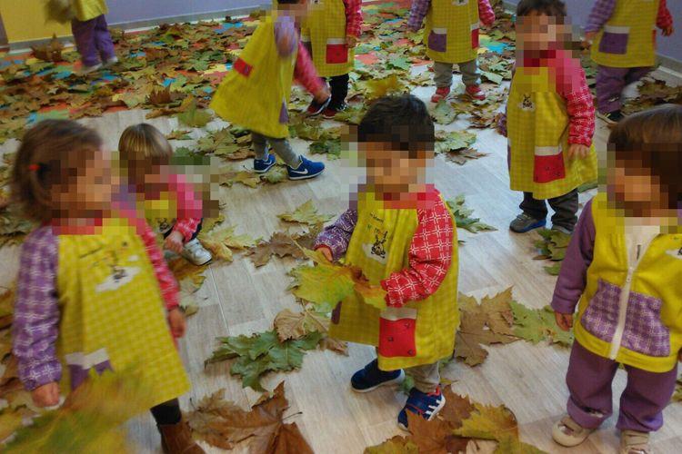 Los niños con las hojas del otoño