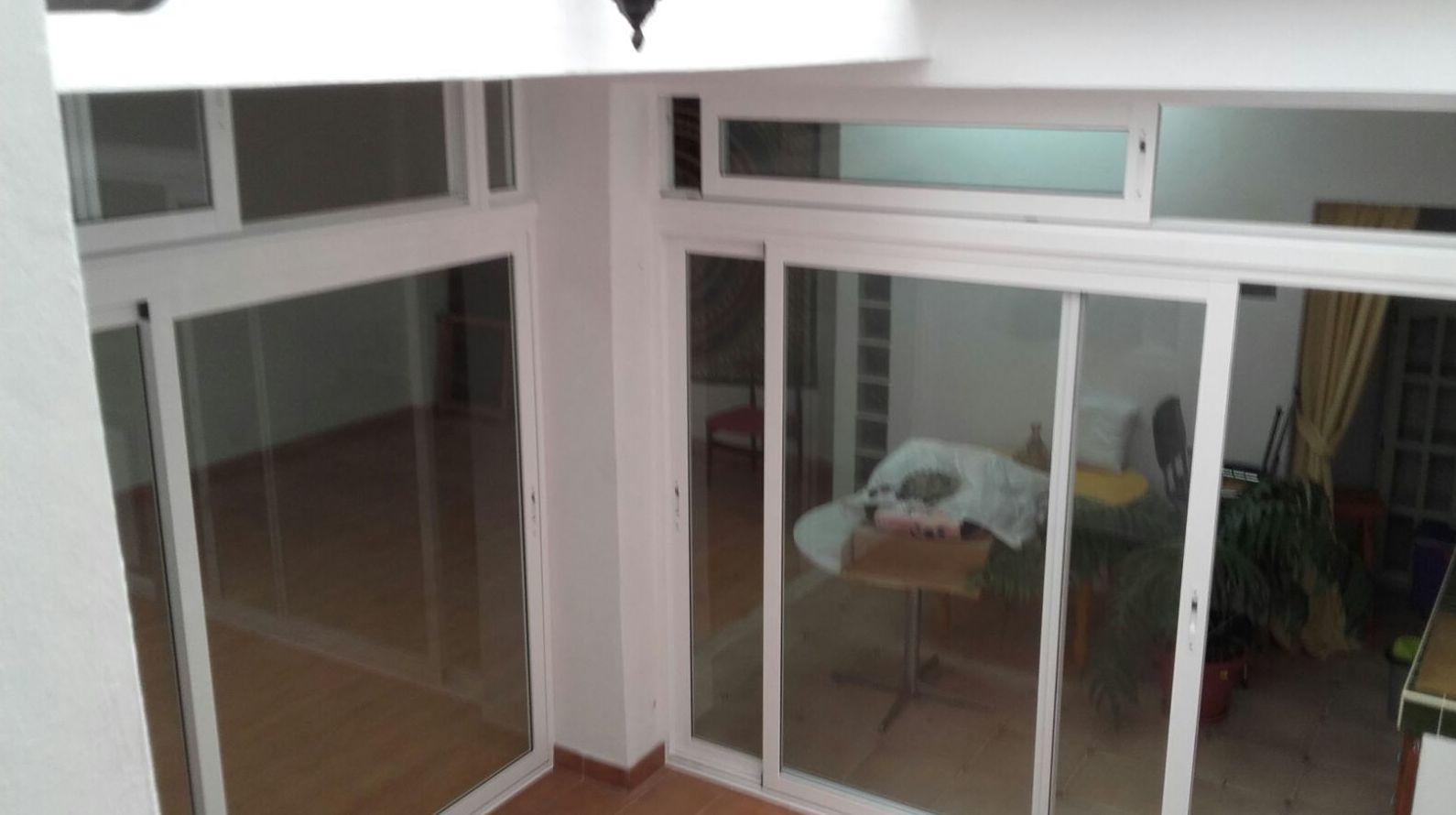 Puerta de corredera con ventanas de corredera en la parte alta