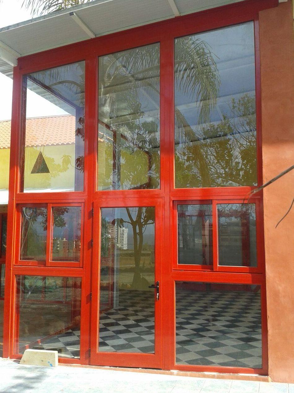 Puerta de entrada con grandes ventanales de aluminio y cristal