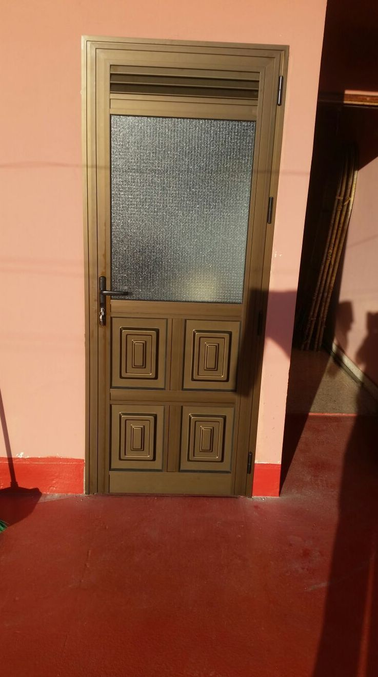 Puerta de aluminio anodizado bronce con cristal armado