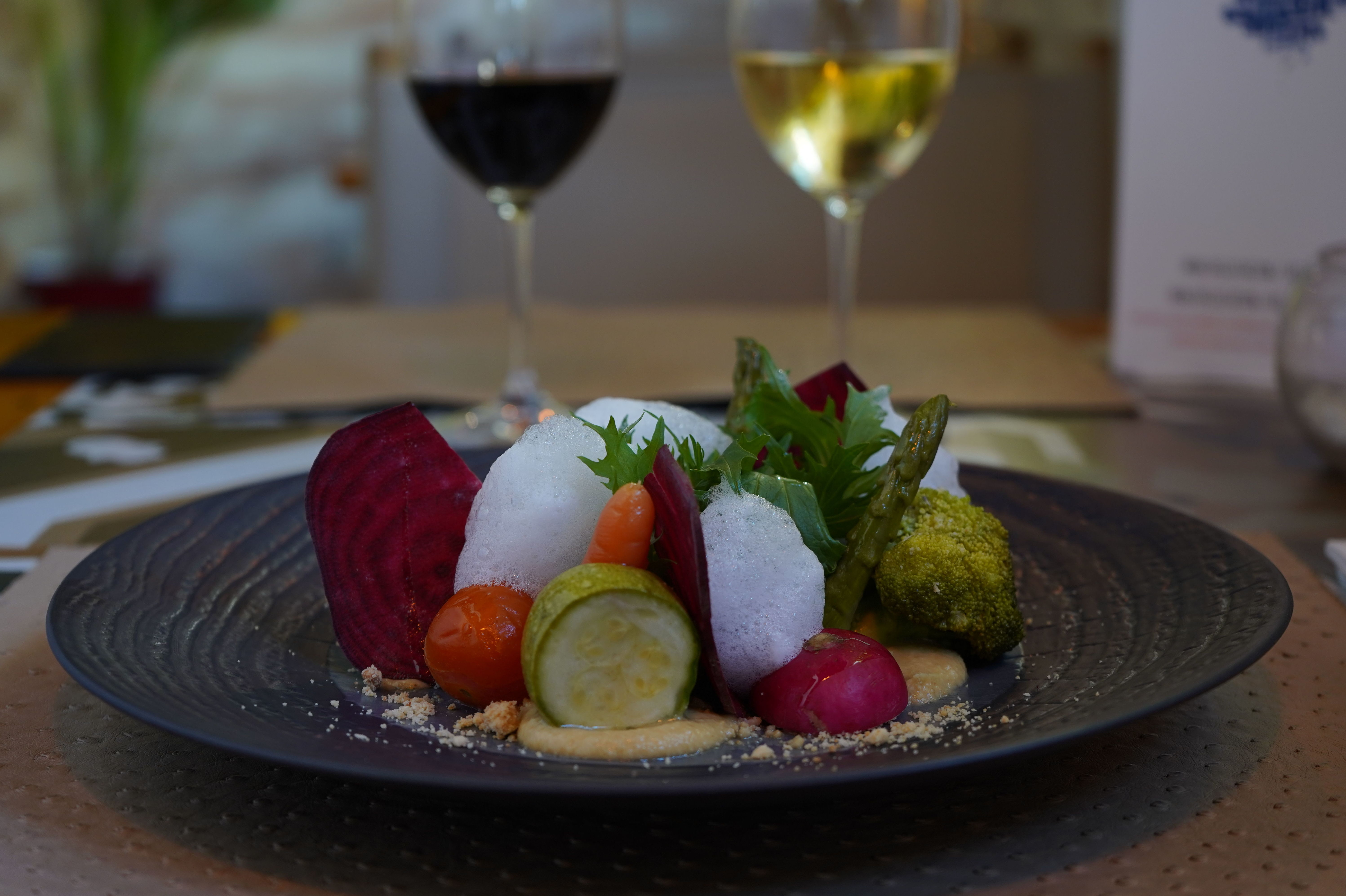 Ensalada Templada de Verduras sobre hummus y tierra de almendras, con aceite de Argán y aire de Haba Tonka